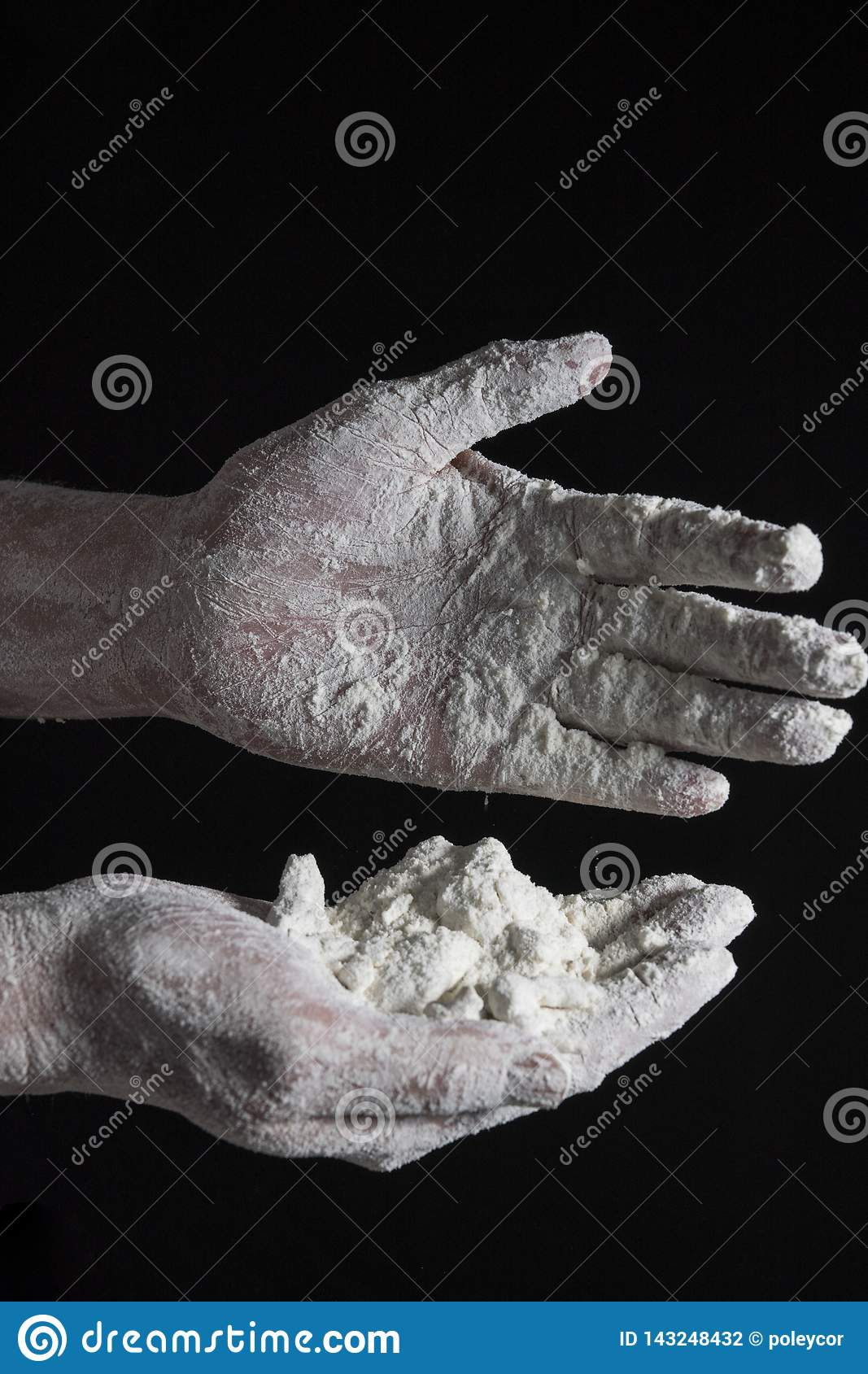 Hand of a cook with dough, against dark background