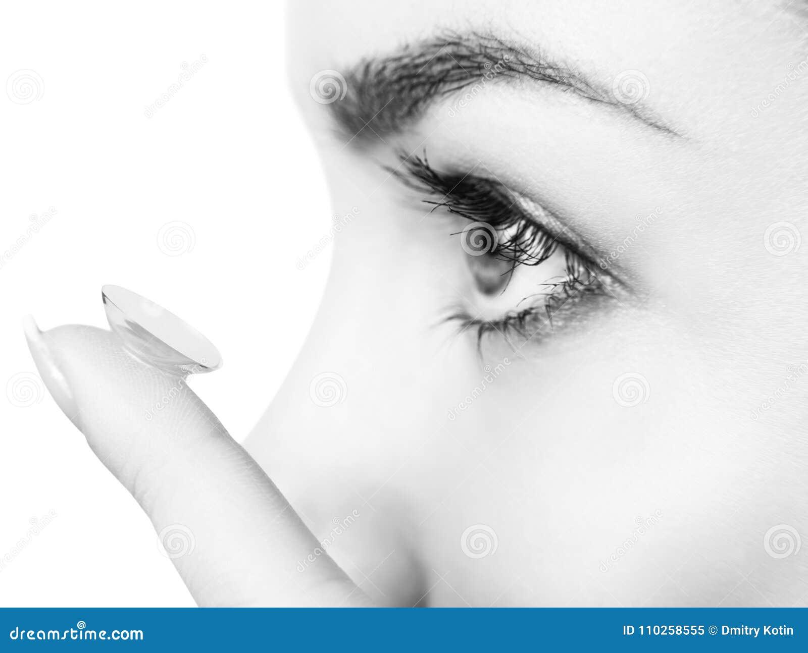 Close-up disparado da lente de contato vestindo da jovem mulher