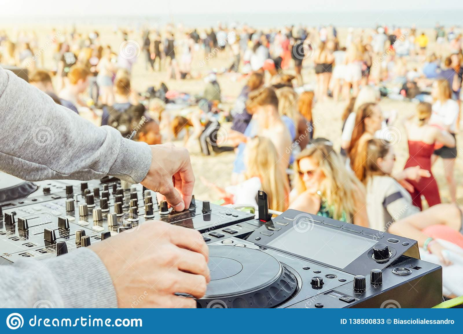 Close up of DJ`s hand playing music at turntable at beach party festival - Crowd people dancing and having fun in club outdoor -