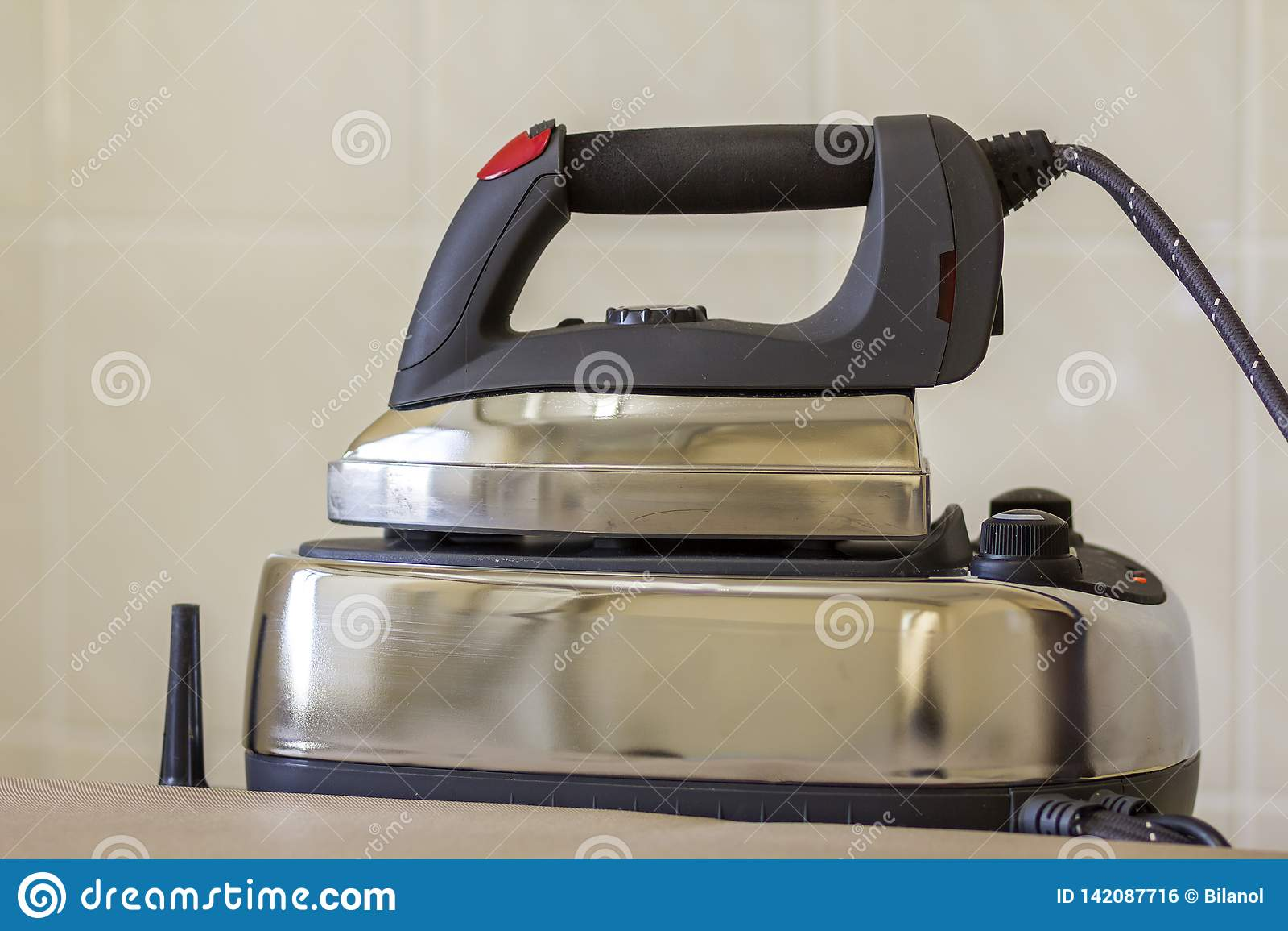 Close-up do ferro de aço inoxidável moderno novo com sola do Teflon e com o gerador de vapor na placa do ferro no espaço claro da