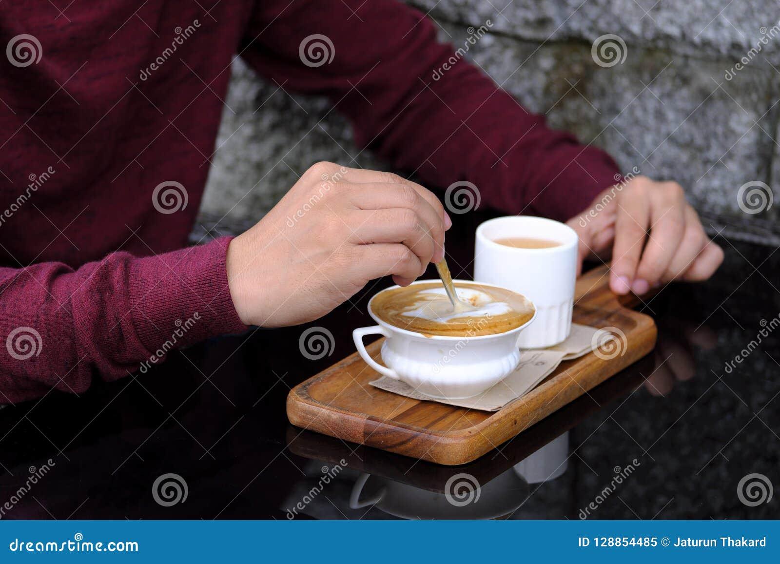 Close up do homem da mão de Ásia na camisa vermelha que agita o açúcar no copo branco pequeno do café quente