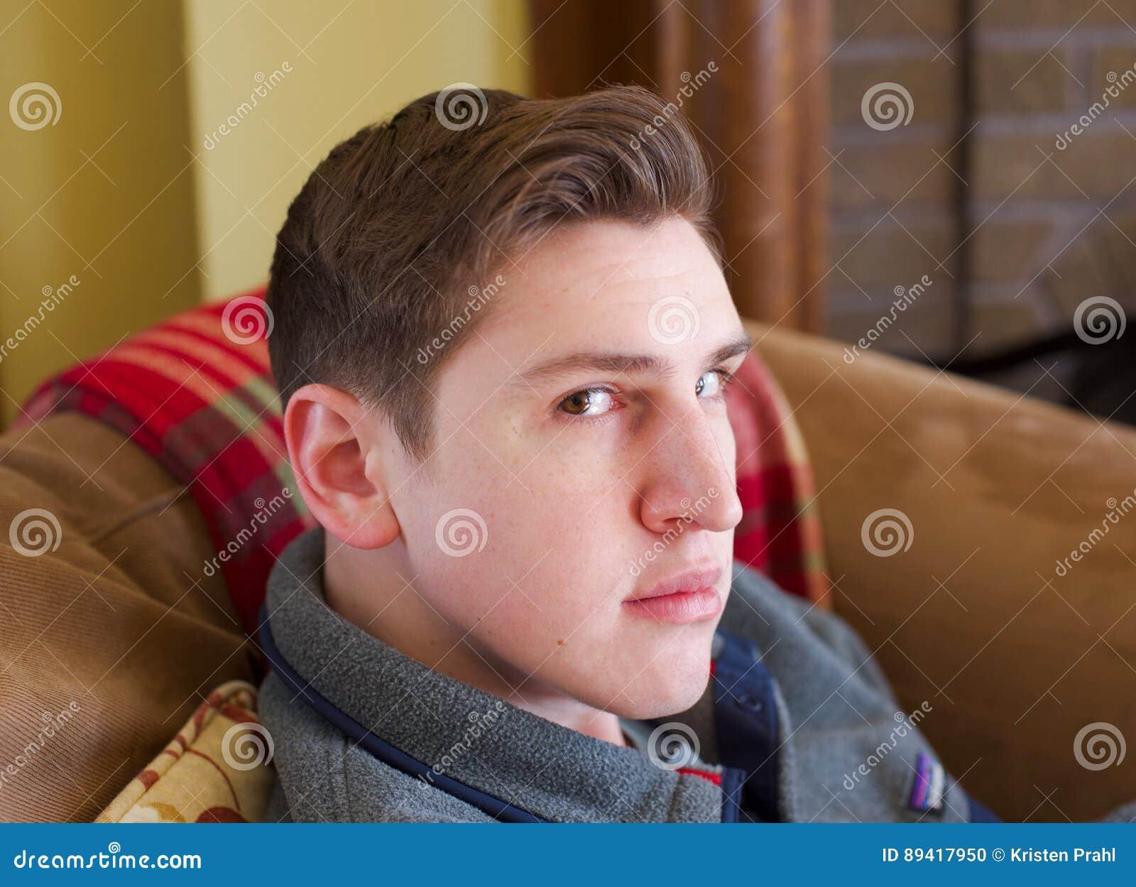 Close up do homem novo que senta-se no sofá que olha a câmera