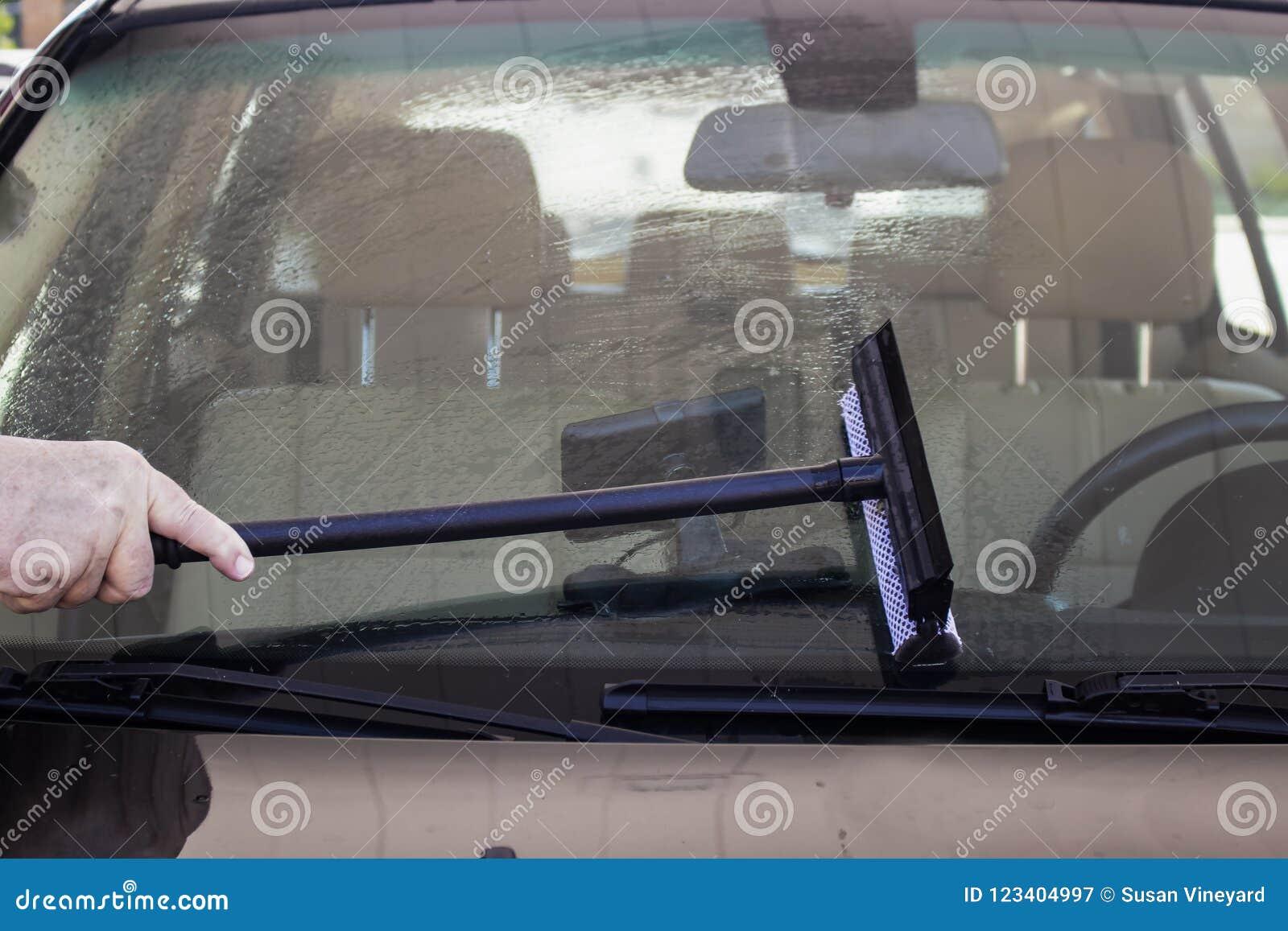 Close-up do homem que usa o rodo de borracha para limpar o para-brisa de um carro com um interior visível de GPS no traço