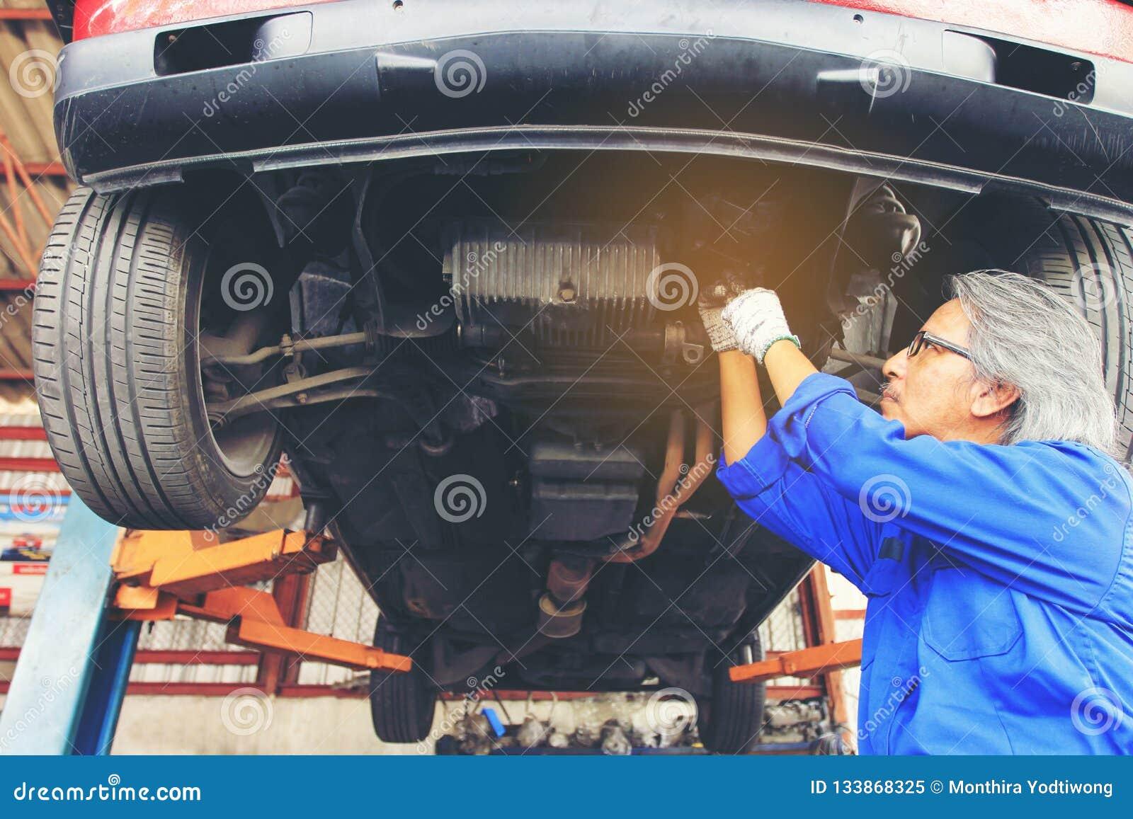Close-up do mecânico de carro que trabalha sob o carro no serviço de reparação de automóveis