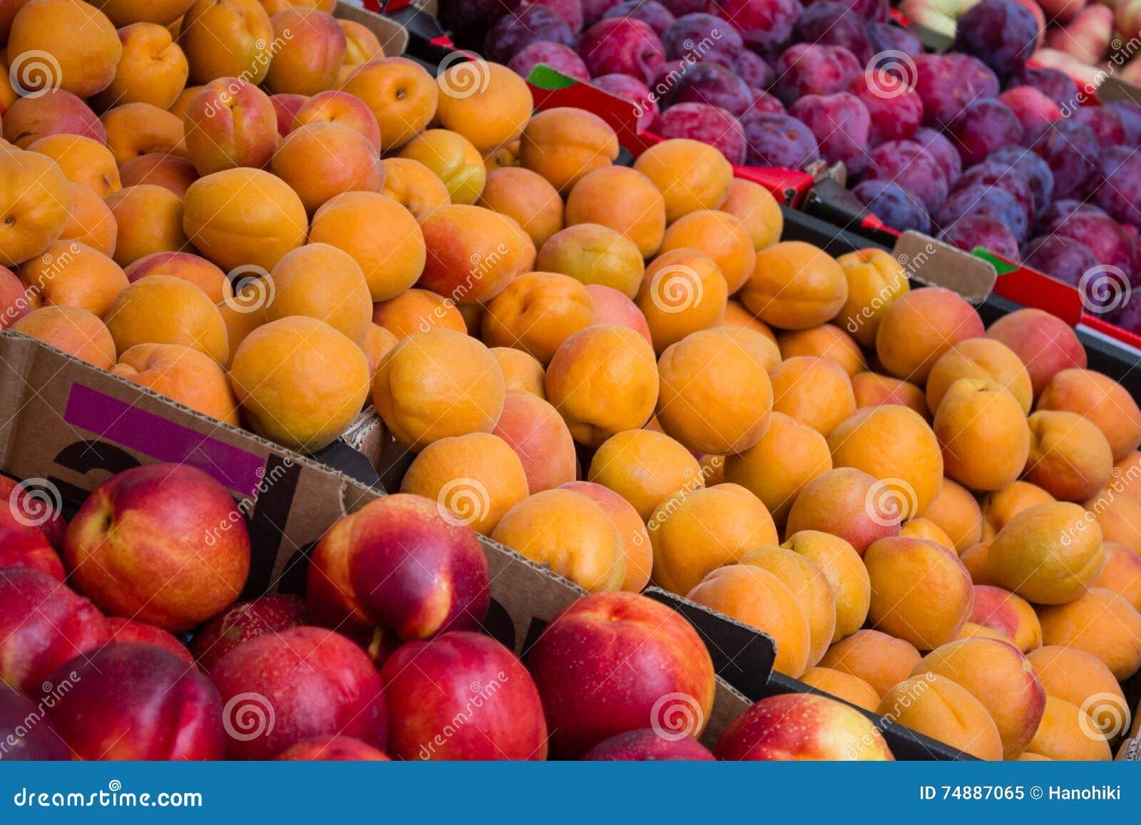 Close up do mercado de fruto - pêssegos, nectarina e ameixas