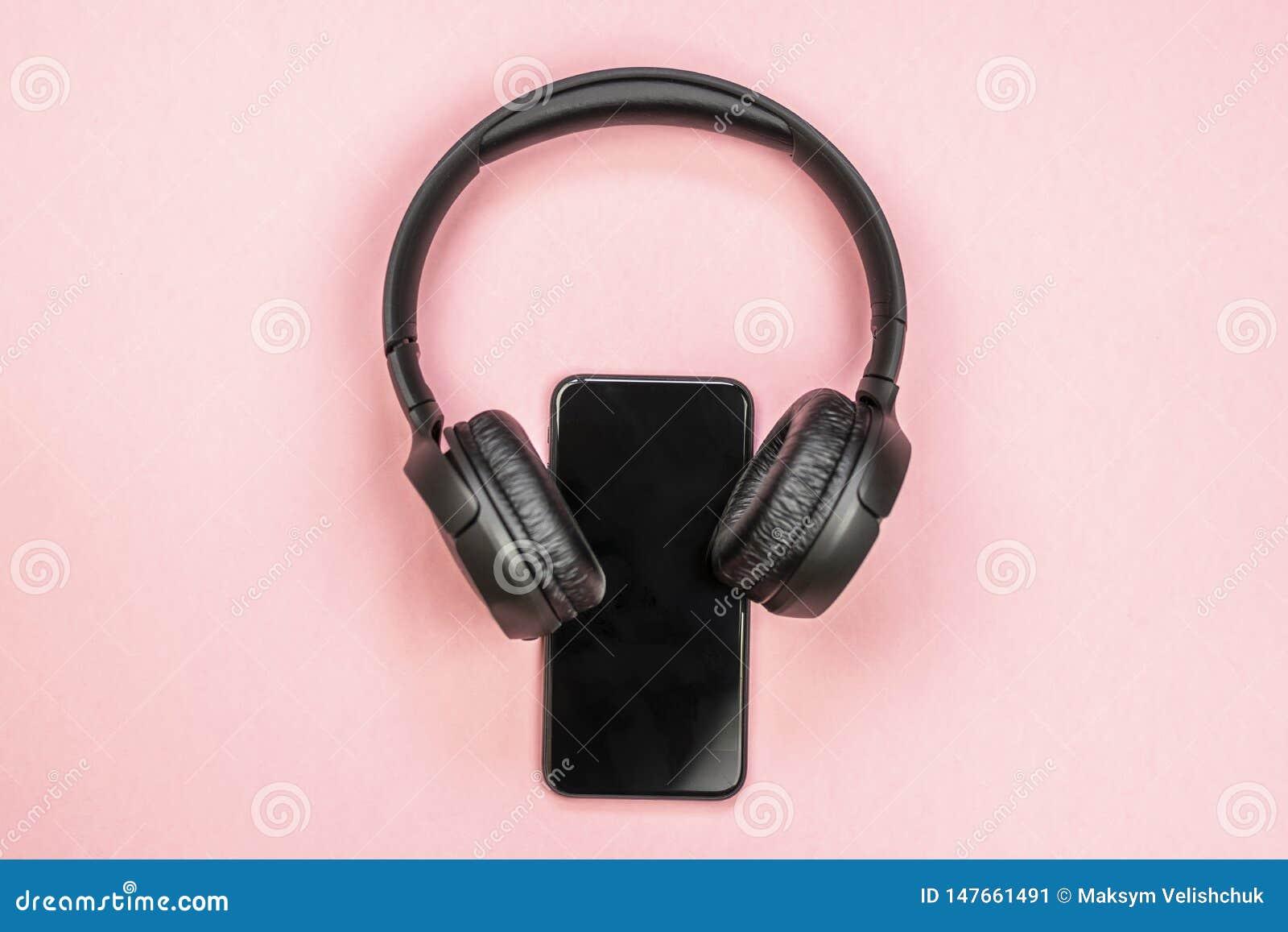 Close-up do telefone esperto com fones de ouvido em um fundo cor-de-rosa