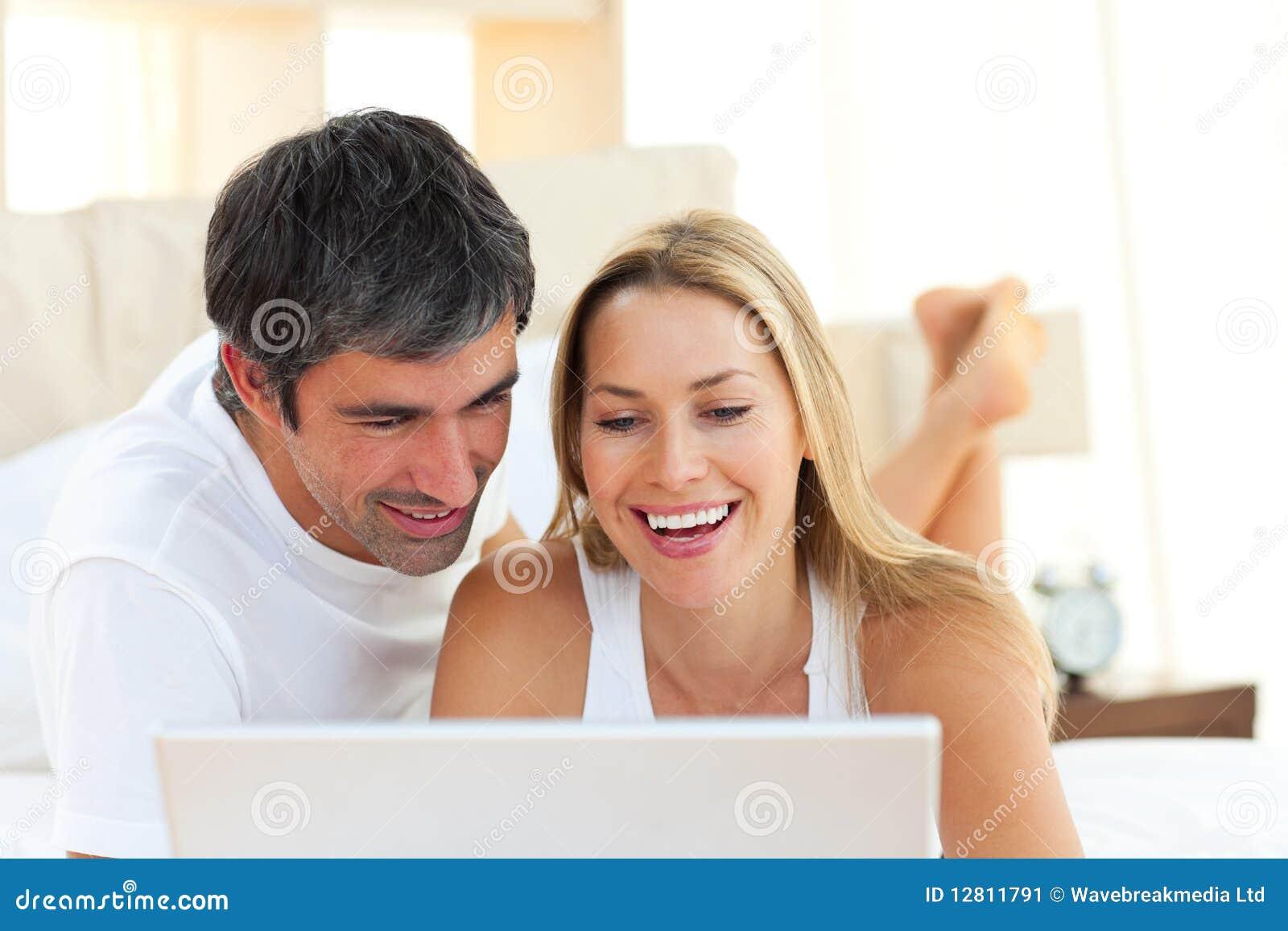 Close-up dos amantes que usam um portátil que encontra-se na cama