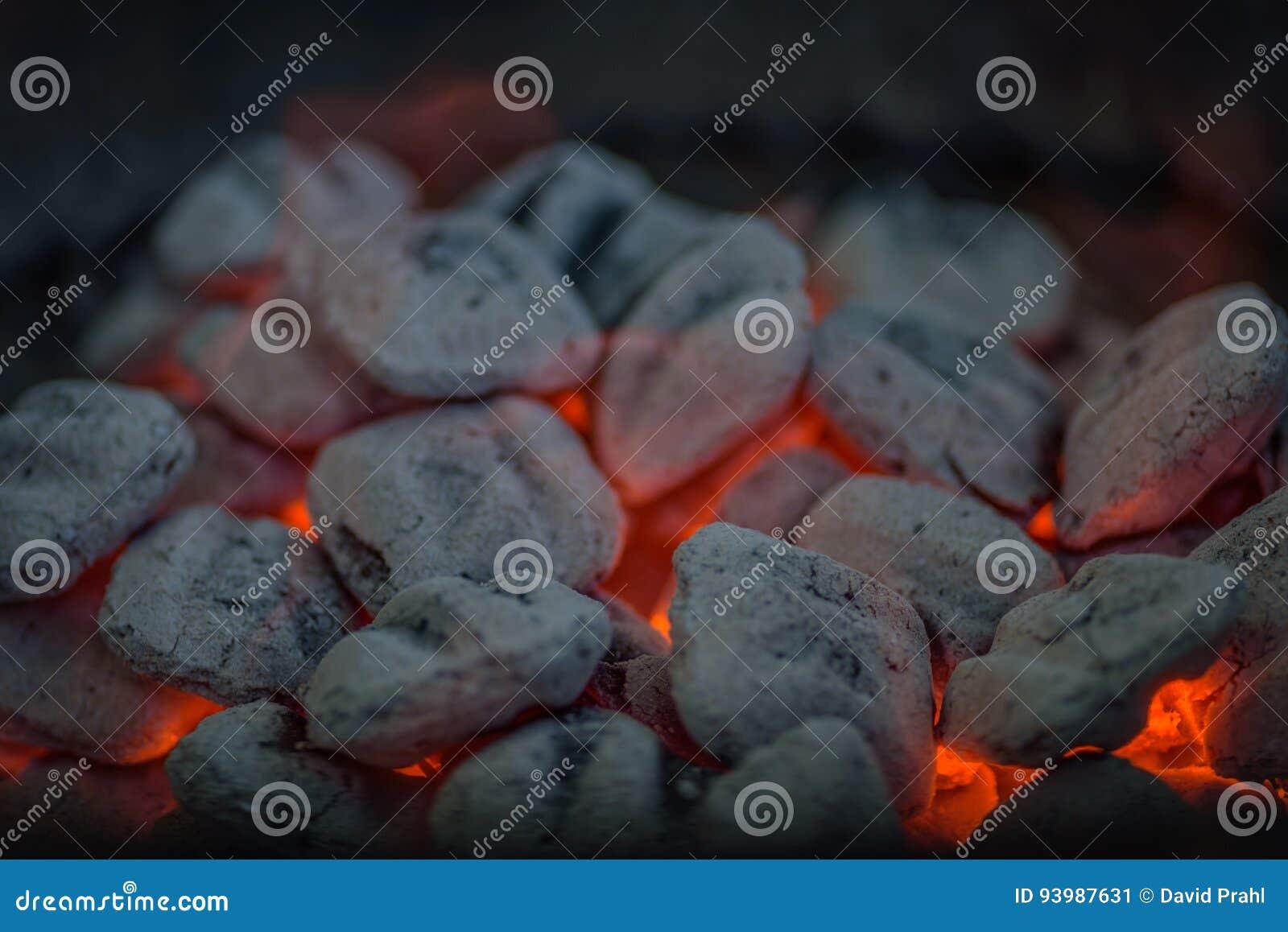 Close up dos carvões amassados quentes brancos do carvão vegetal na grade do assado