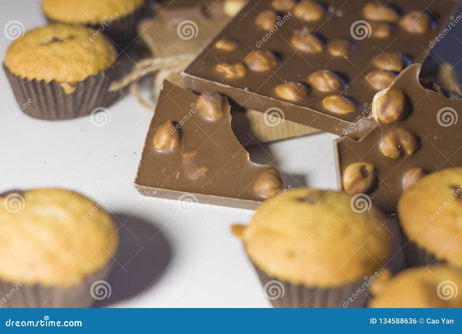 Close up dos doces, do chocolate com porcas e dos queques em um fundo branco