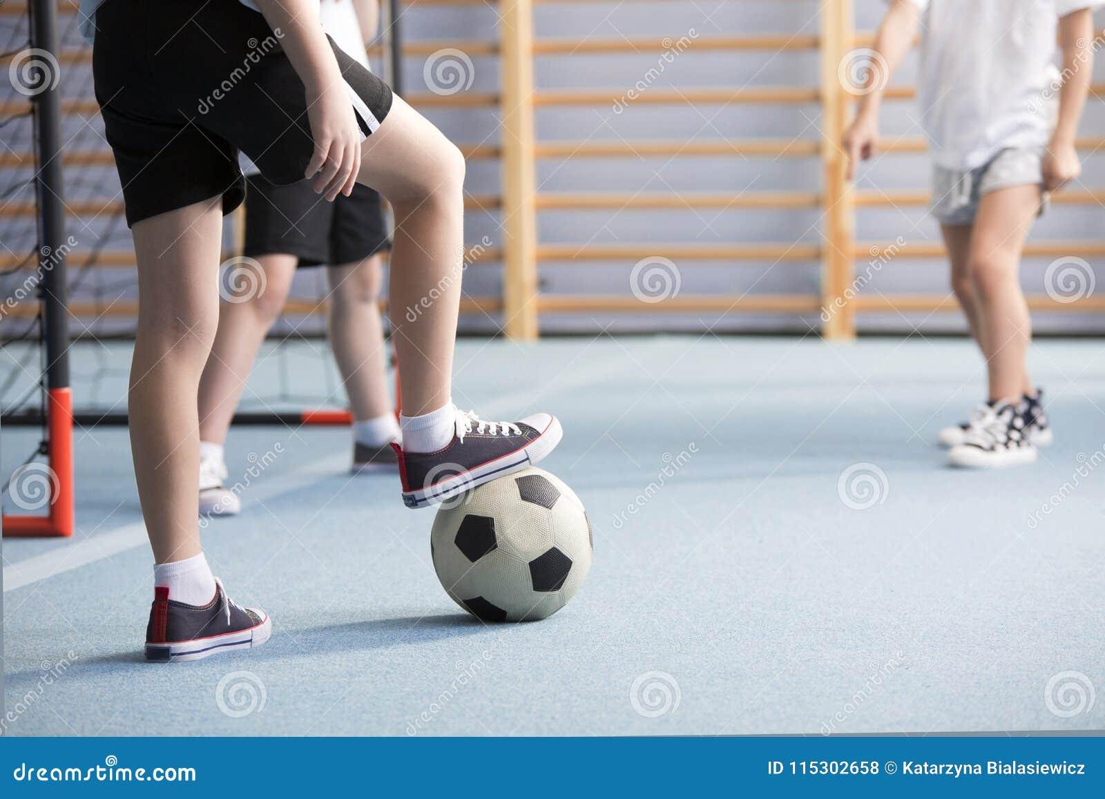 Close-up dos meninos que jogam o futebol