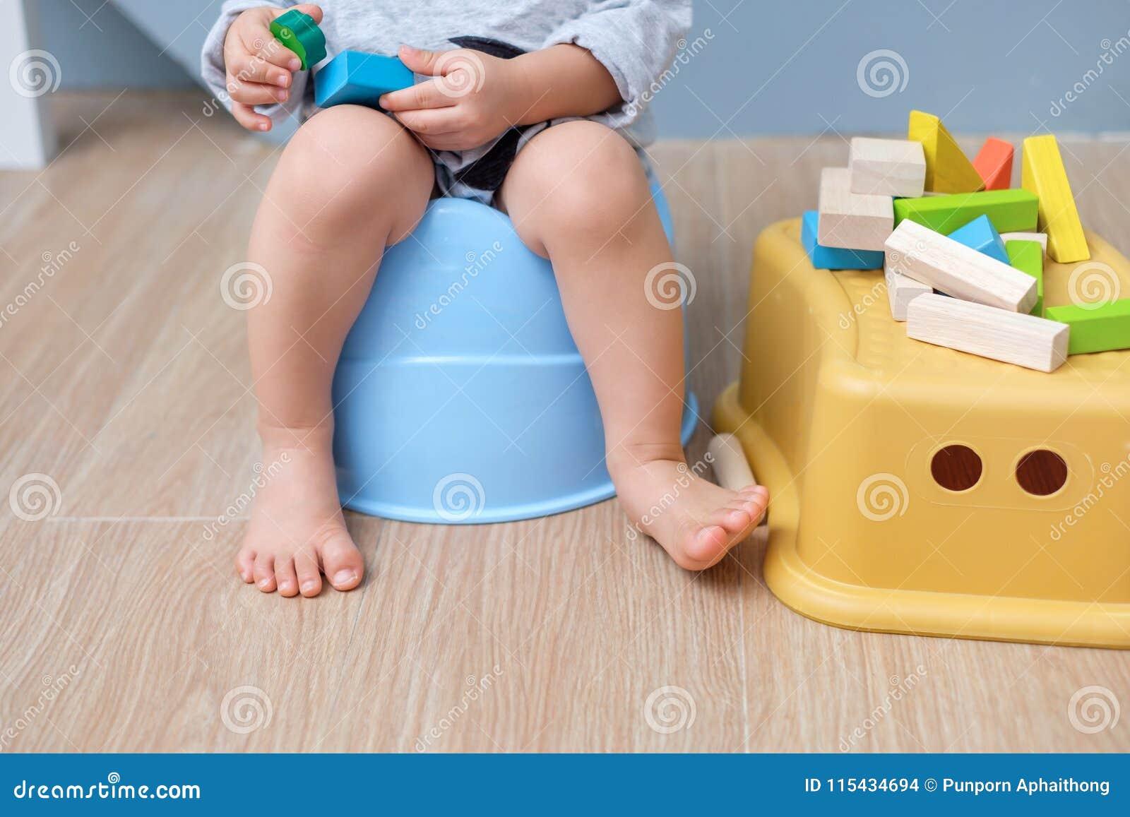 Close up dos pés do menino da criança que sentam-se no urinol