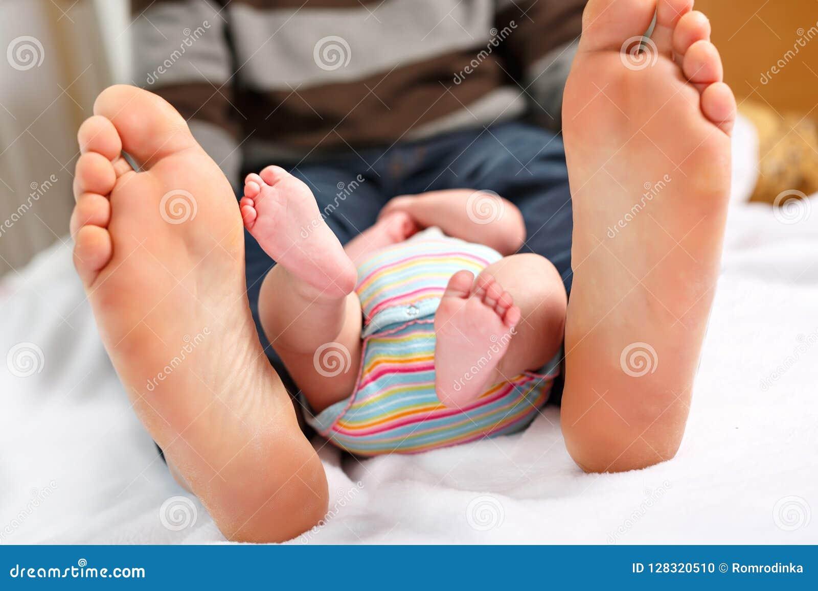 Close up dos pés enormes do pai e do bebê recém-nascido pequeno