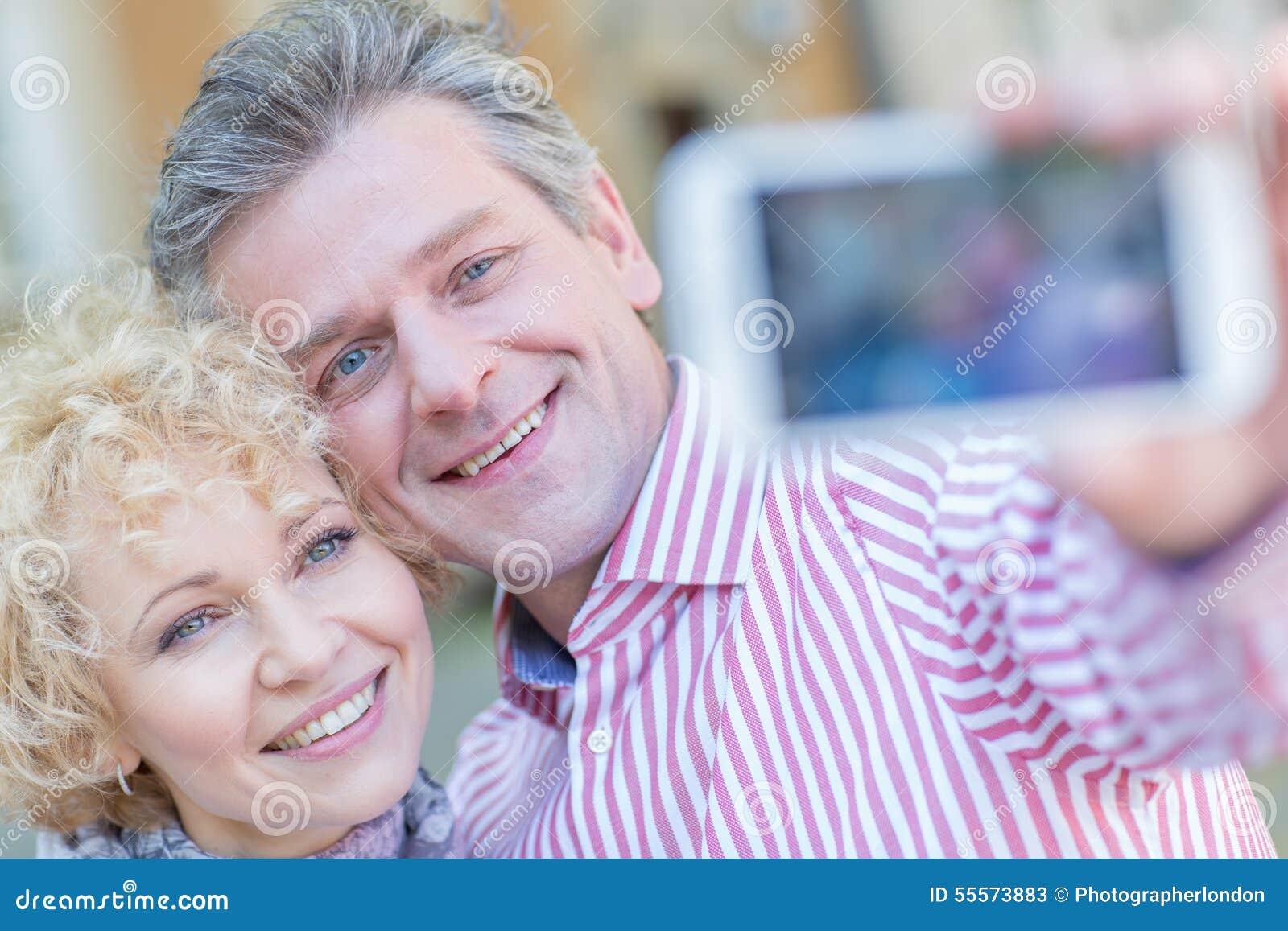 Close-up dos pares de meia idade felizes que tomam o selfie através do telefone esperto