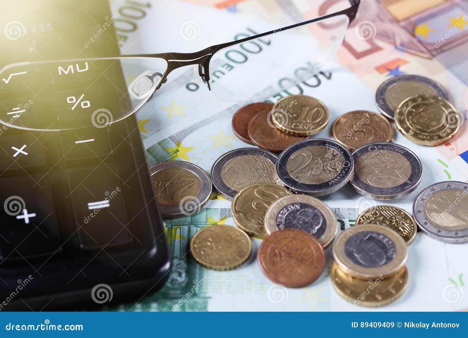 Close up dos vidros em euro- cédulas com moedas e calculadora Conceito do negócio