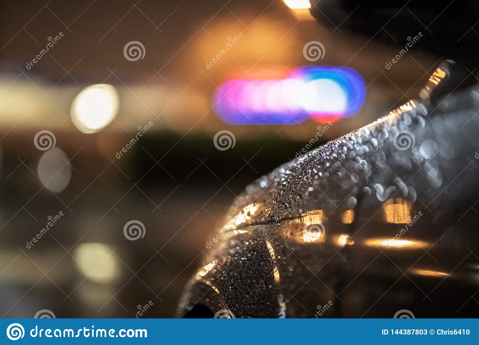Close up of a dramatic black car at night, waiting in street lights in the heavy rain
