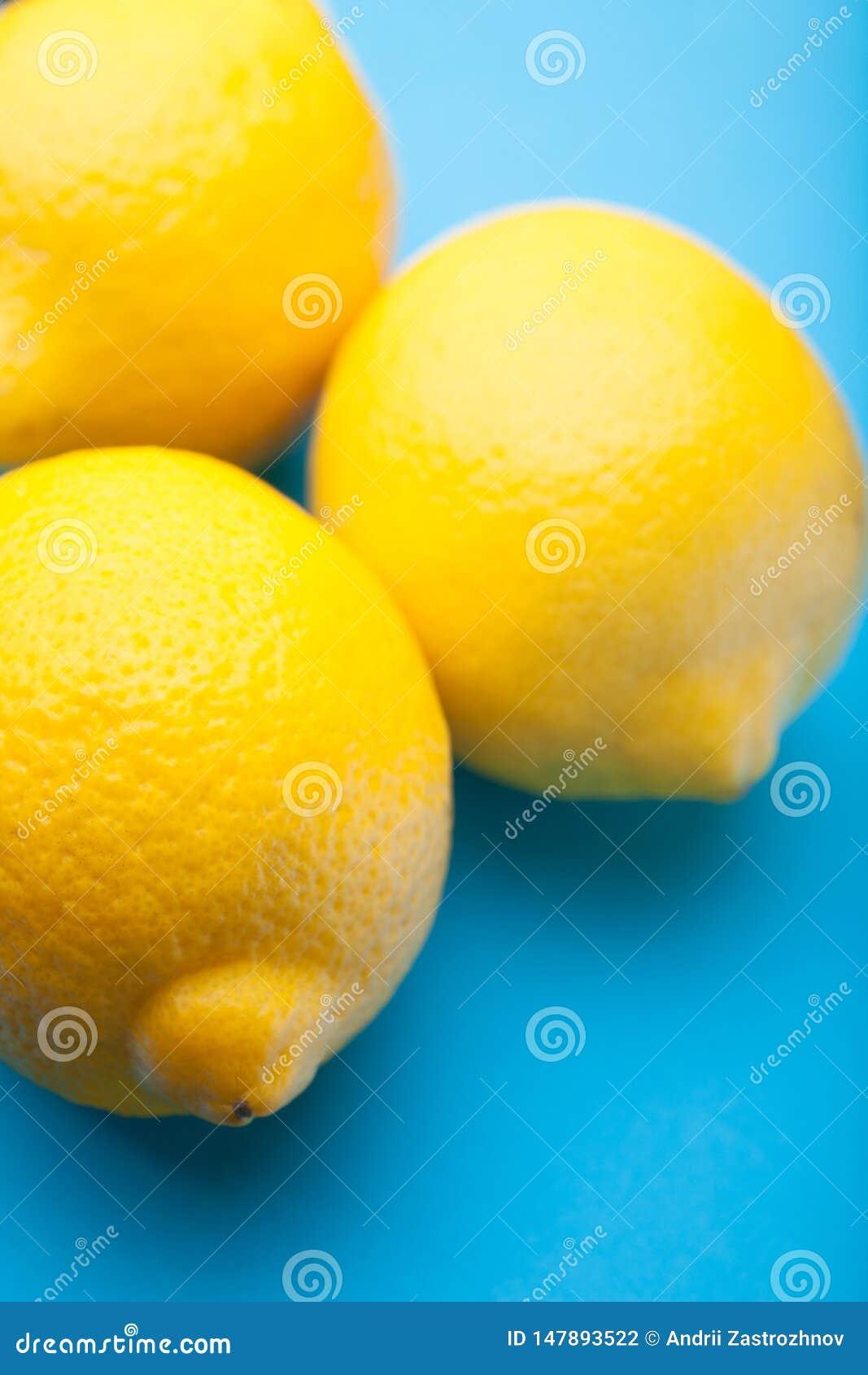 Close-up, drie gele citroenen op een blauwe achtergrond