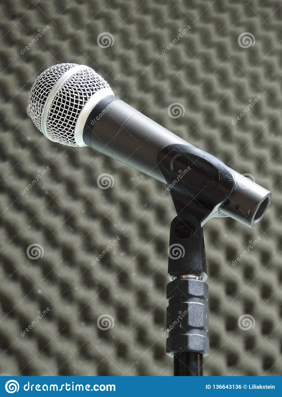 Close-up of a dynamic vocal microphone. Blurred background of acoustic foam.