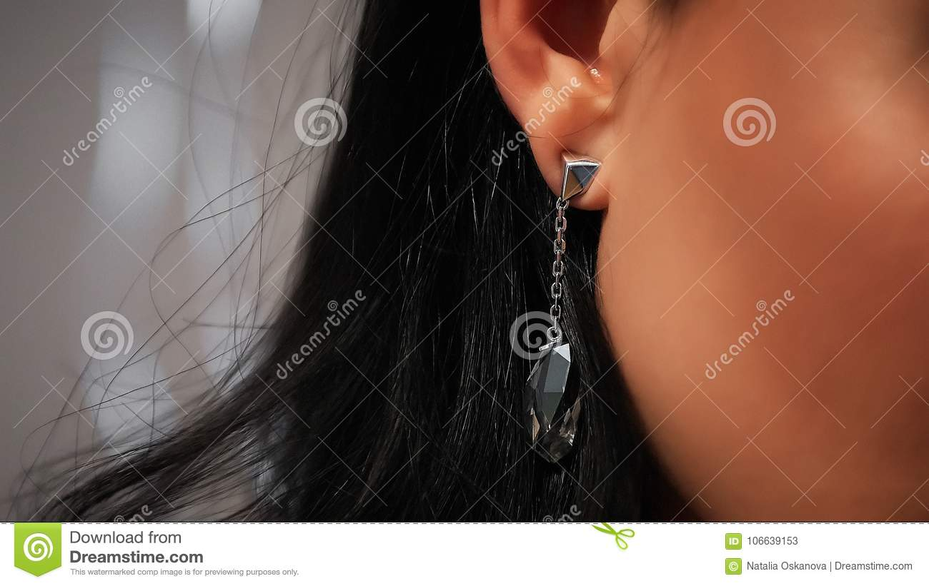 Close up earring in ear of black-haired woman