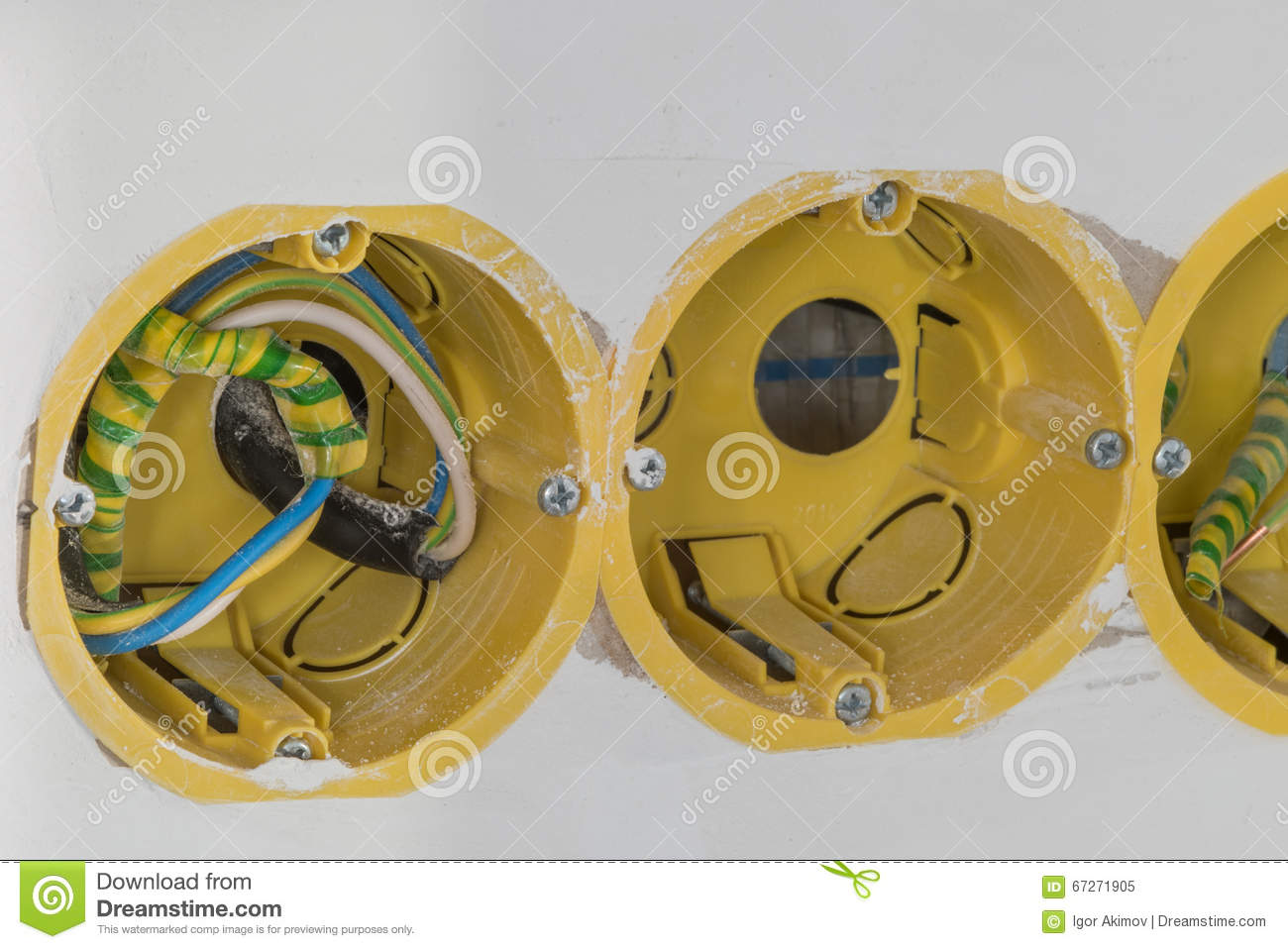 Close Up Electrical Distribution System Installation In New Buil Multiple Receptacles On The Same Circuit Are Connected Household Box For Connecting An Outlet A Residential Building White Unpainted Wall Of Yellow Color With Wires During