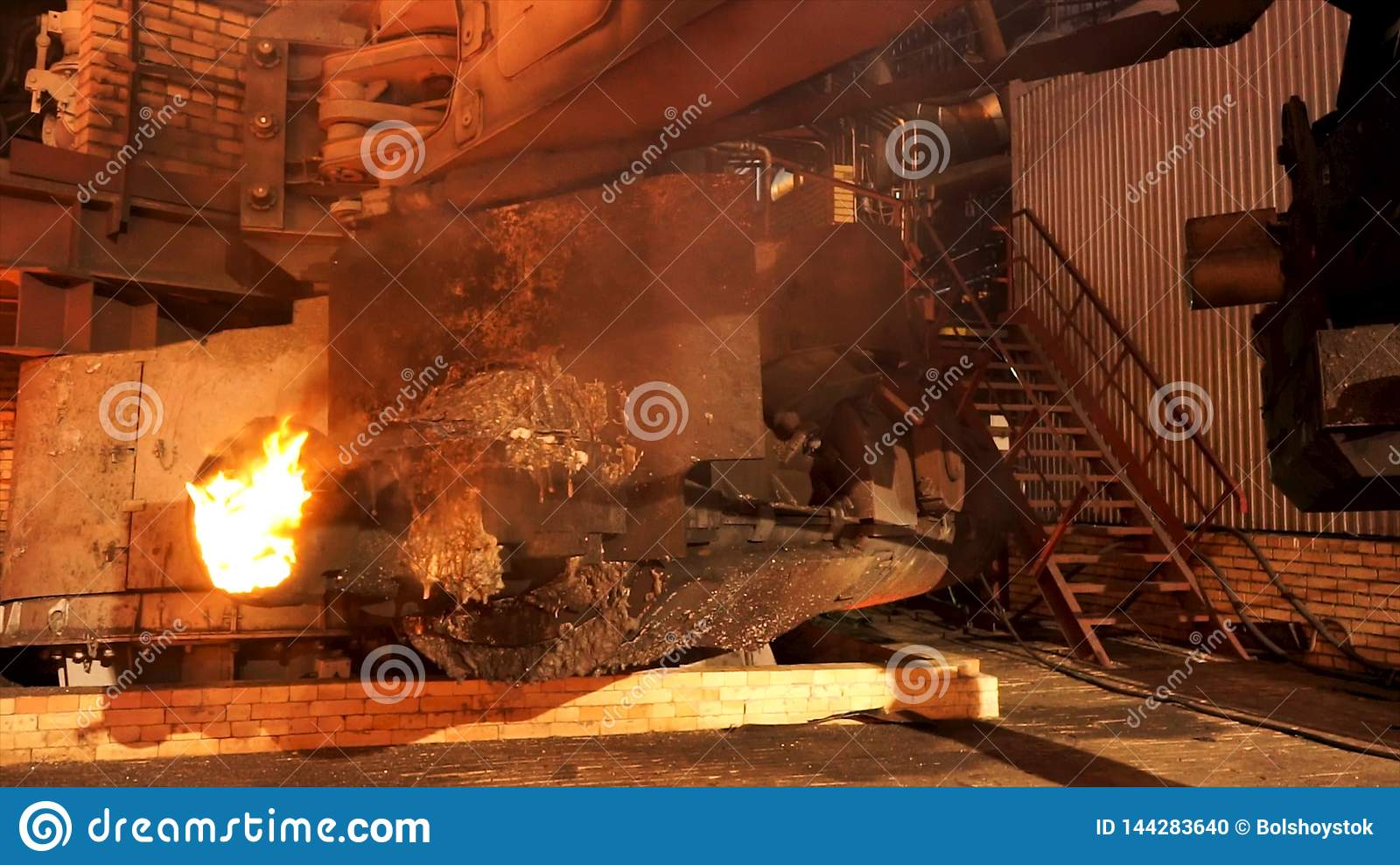 Close up for the equipment at the metallurgical plant with burning furnace melting steel. Stock footage. Shop at the
