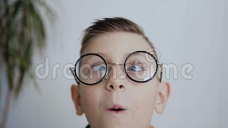 b45c427f7ab9 Close-up of the face of a little boy who has strabismus eyes and poor  eyesight and he wears glasses to see better. The. Royalty-Free Stock Footage