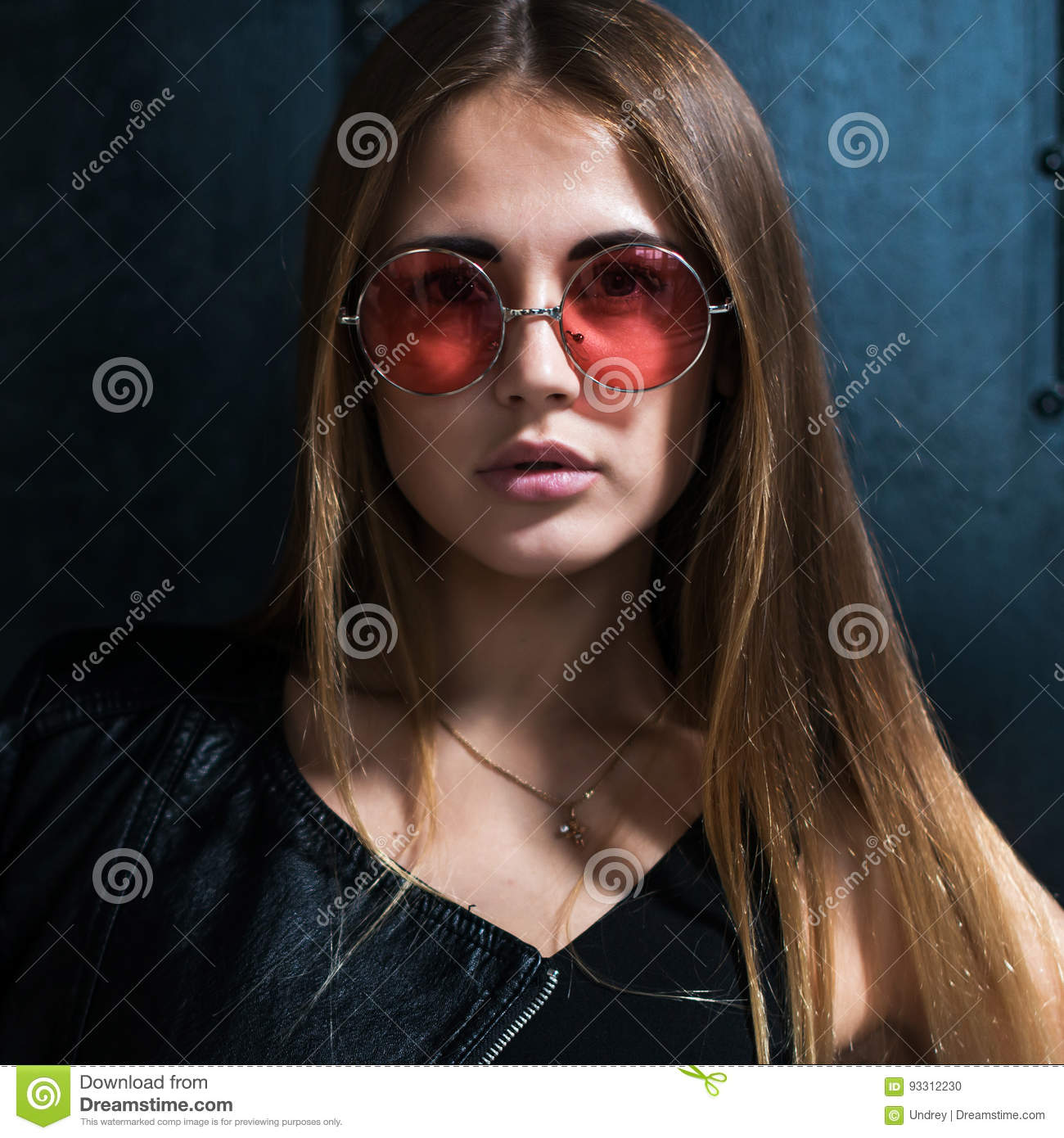 Close up face portrait of beautiful Caucasian young woman with loose hair in fashionable pink round sunglasses looking
