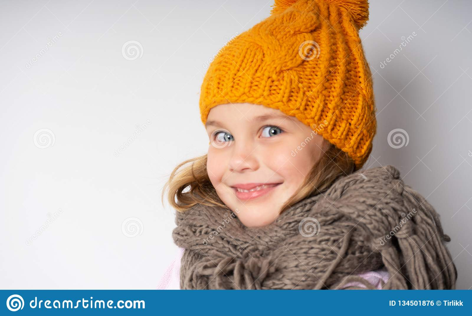 611f014dfa6 Close up face portrait of toothy smiling young woman wearing knitted hat  and scarf.