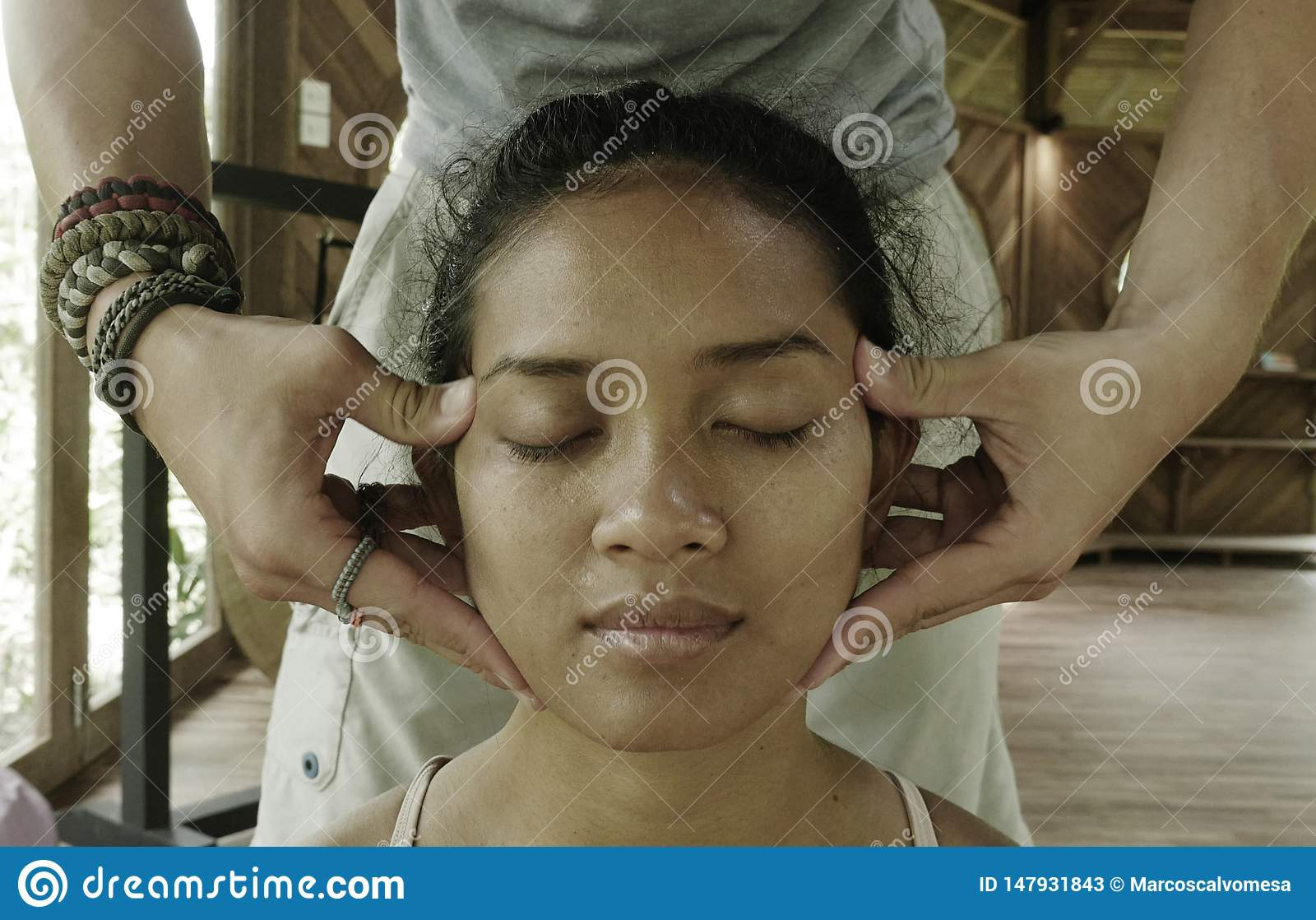 Close up face portrait of young gorgeous and relaxed Asian Indonesian woman receiving traditional facial Thai massage with male