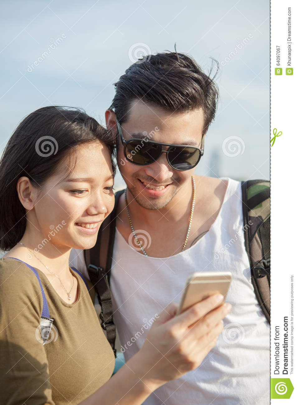 Close up face of younger asian man and woman looking to smart ph