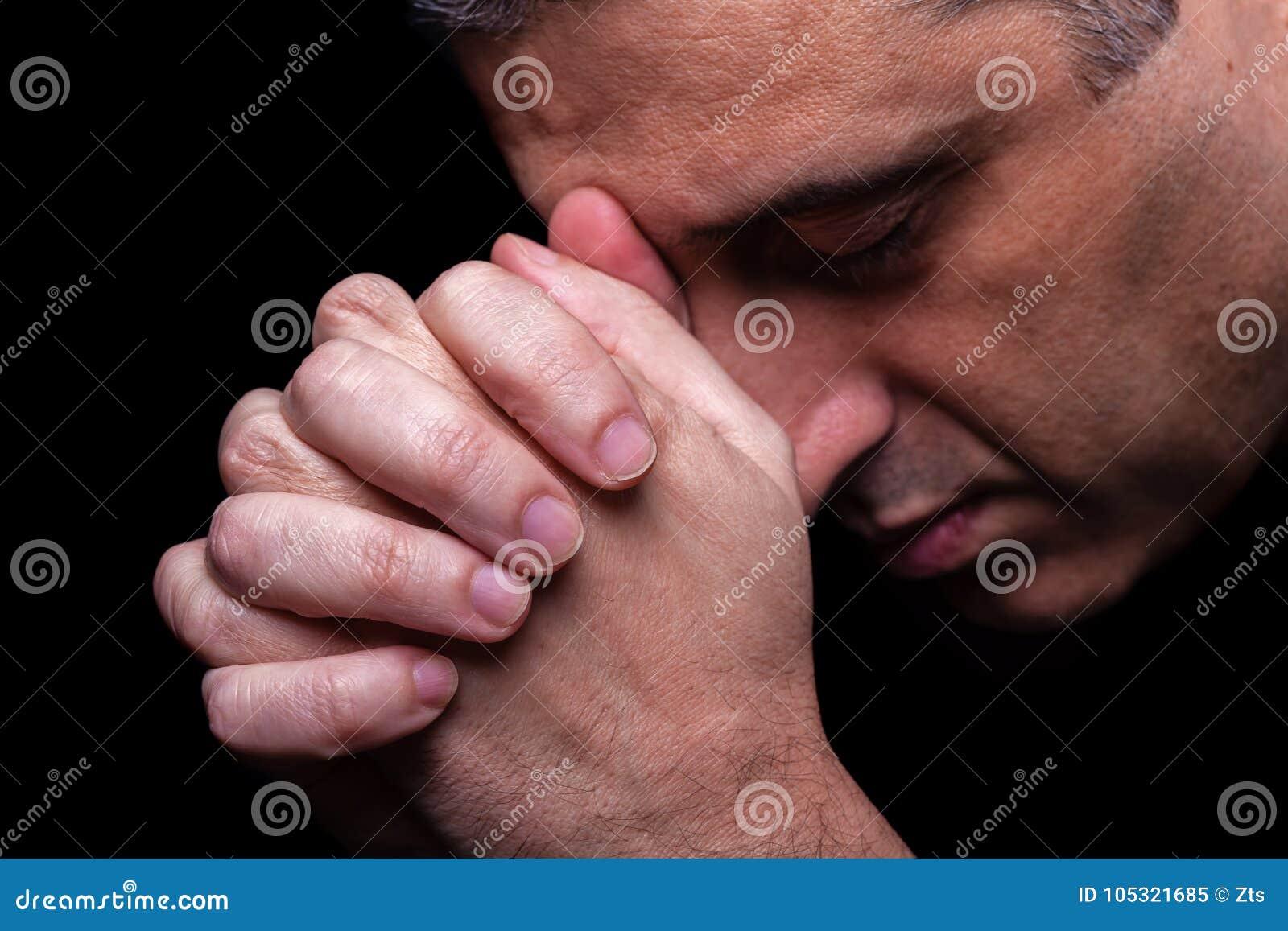 Close up of faithful mature man praying, hands folded in worship to god