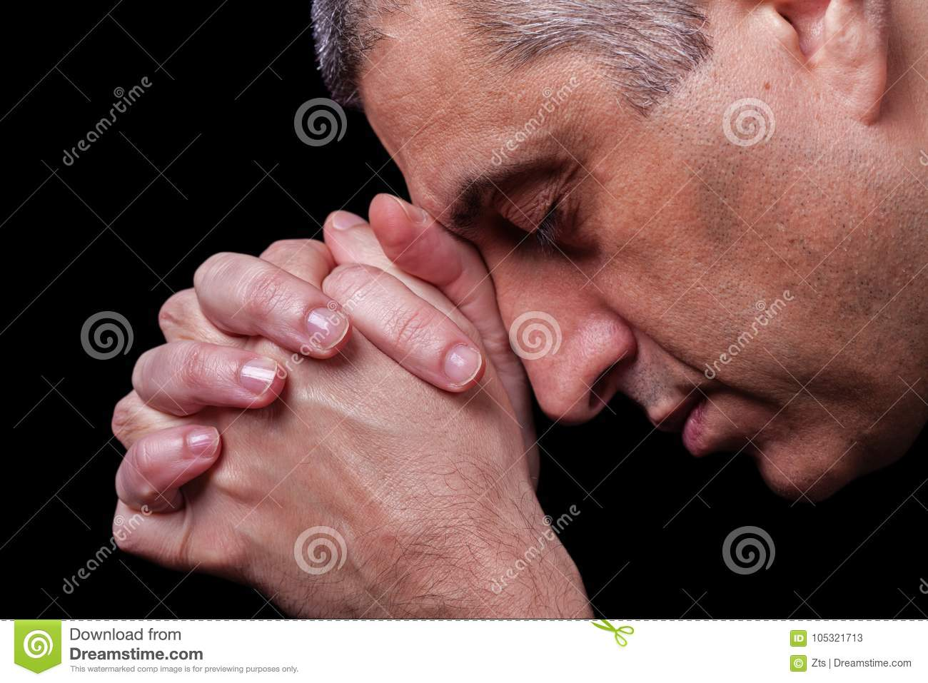Close up of faithful mature man praying, hands folded in worship to god