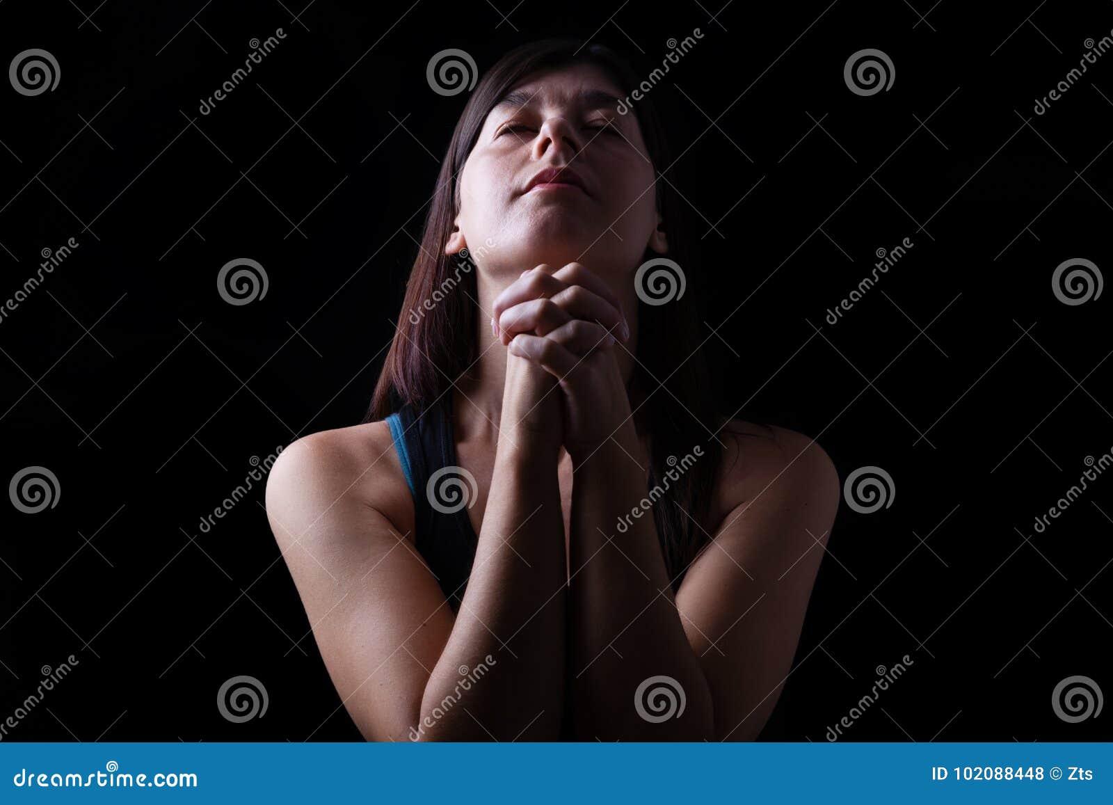 Faithful woman praying, hands folded in worship