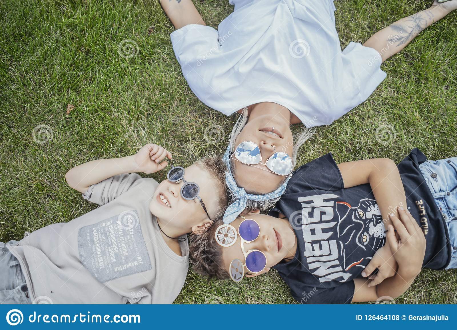 Close up of family lying on green grass. View from above. Happy family concept.