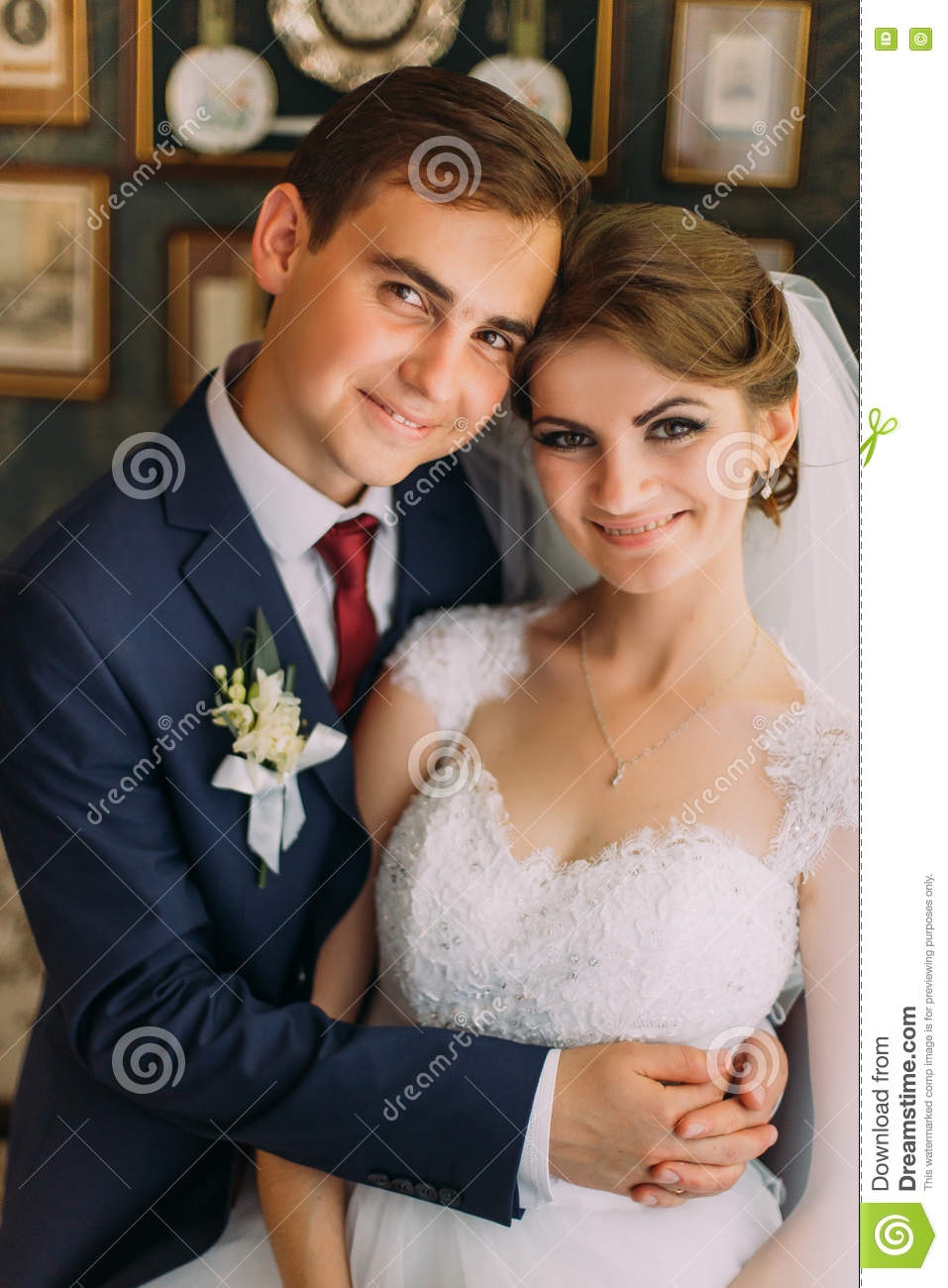 Close-up family photo of bride and groom posing in restaurant with vintage interior