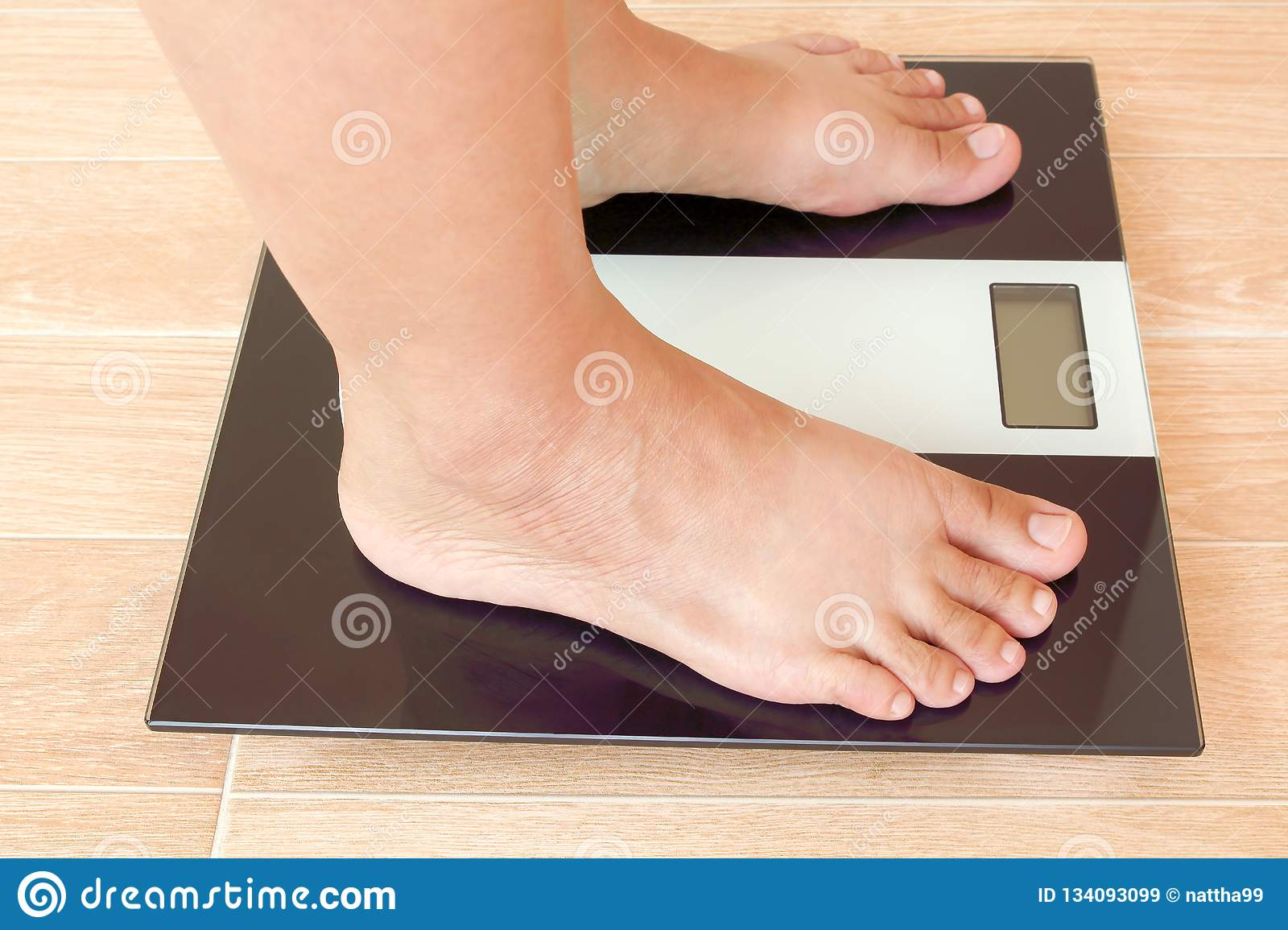 Close up of fat female feet standing on weight scale