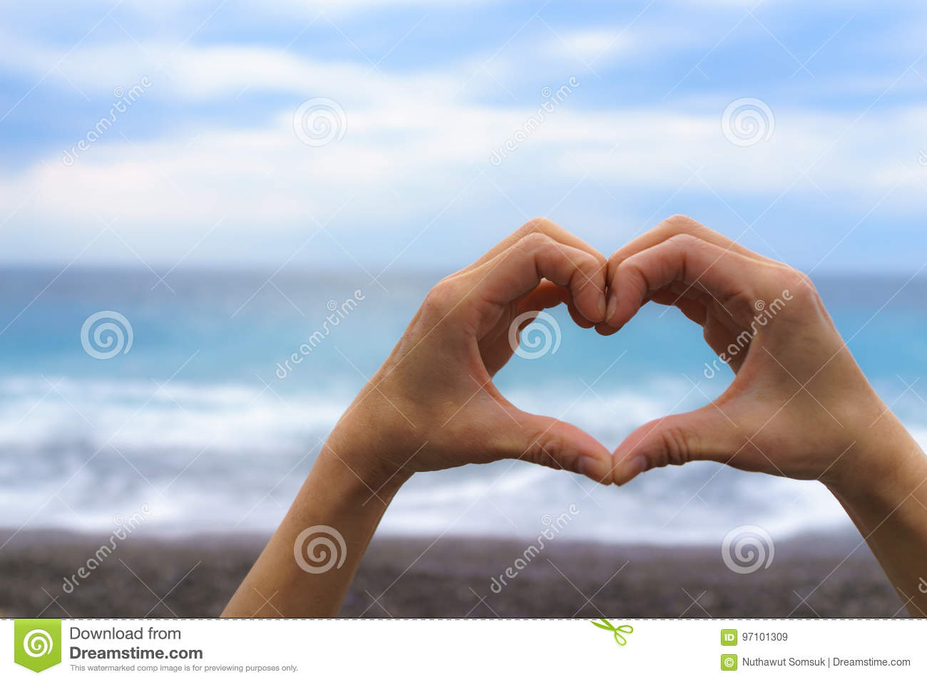 Close up of female hand making heart shape with blue sea and sky