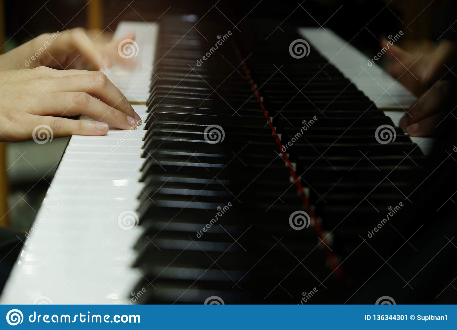 Close-up female hand playing grand piano