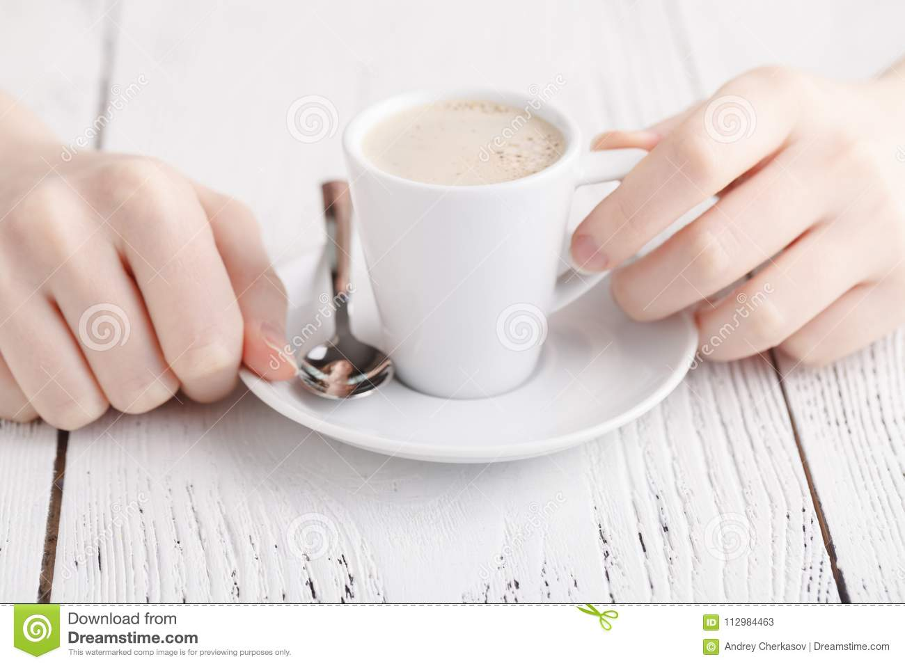 Close up female hands with cup of coffee on the table. coffee break closeup