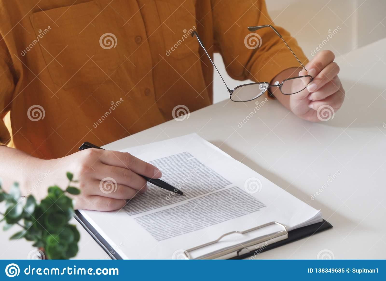 Close-up of female hands. writing something and holding glasses in her office