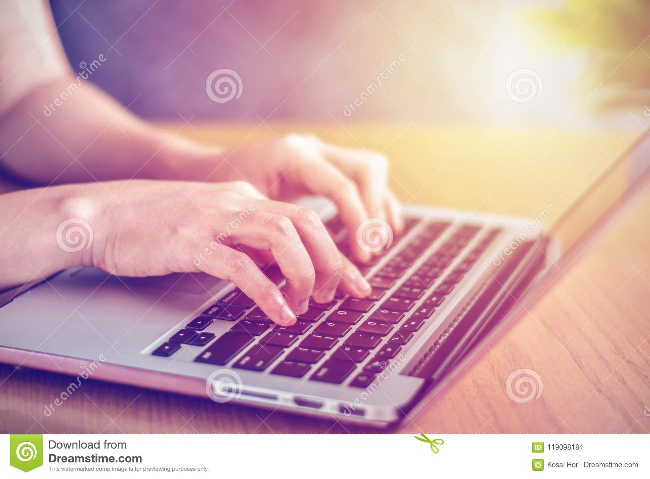 Close-up of a female`s hands typing a laptop`s keyboard