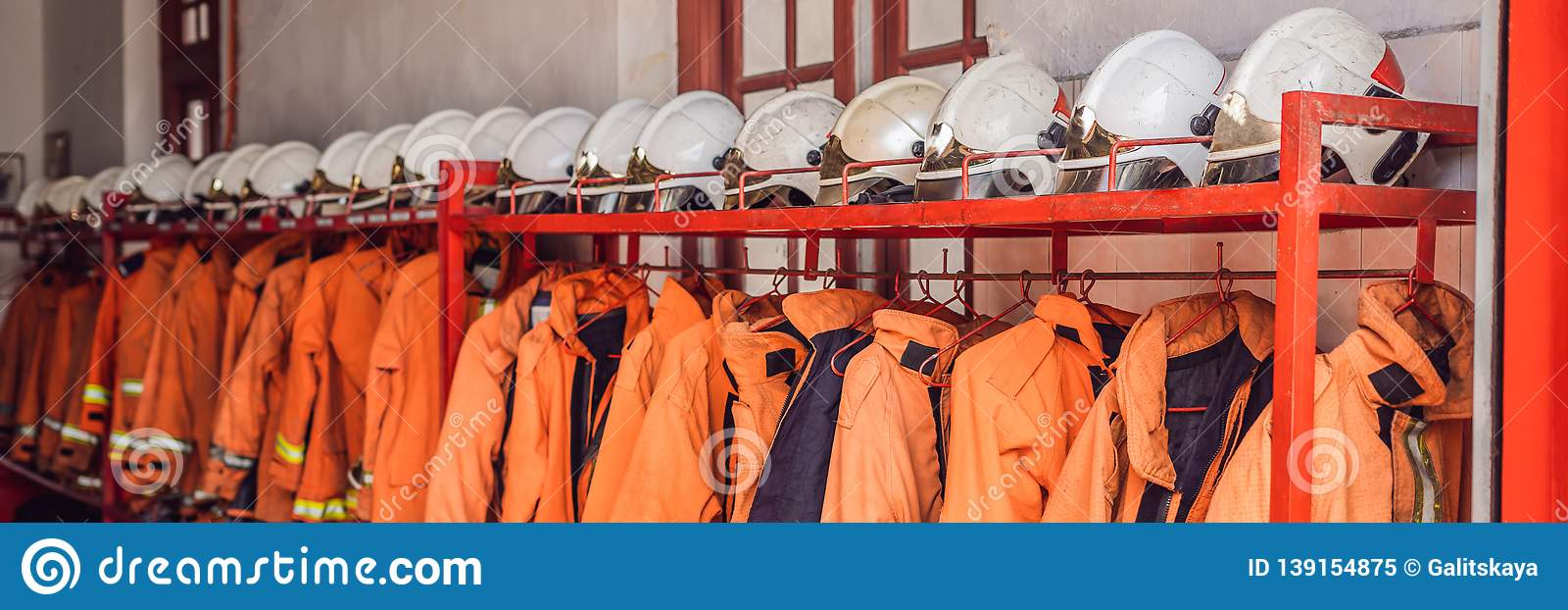 Close up of Fireman coats, helmets and boots wait for the next call. Dressing room of the volunteer fire department