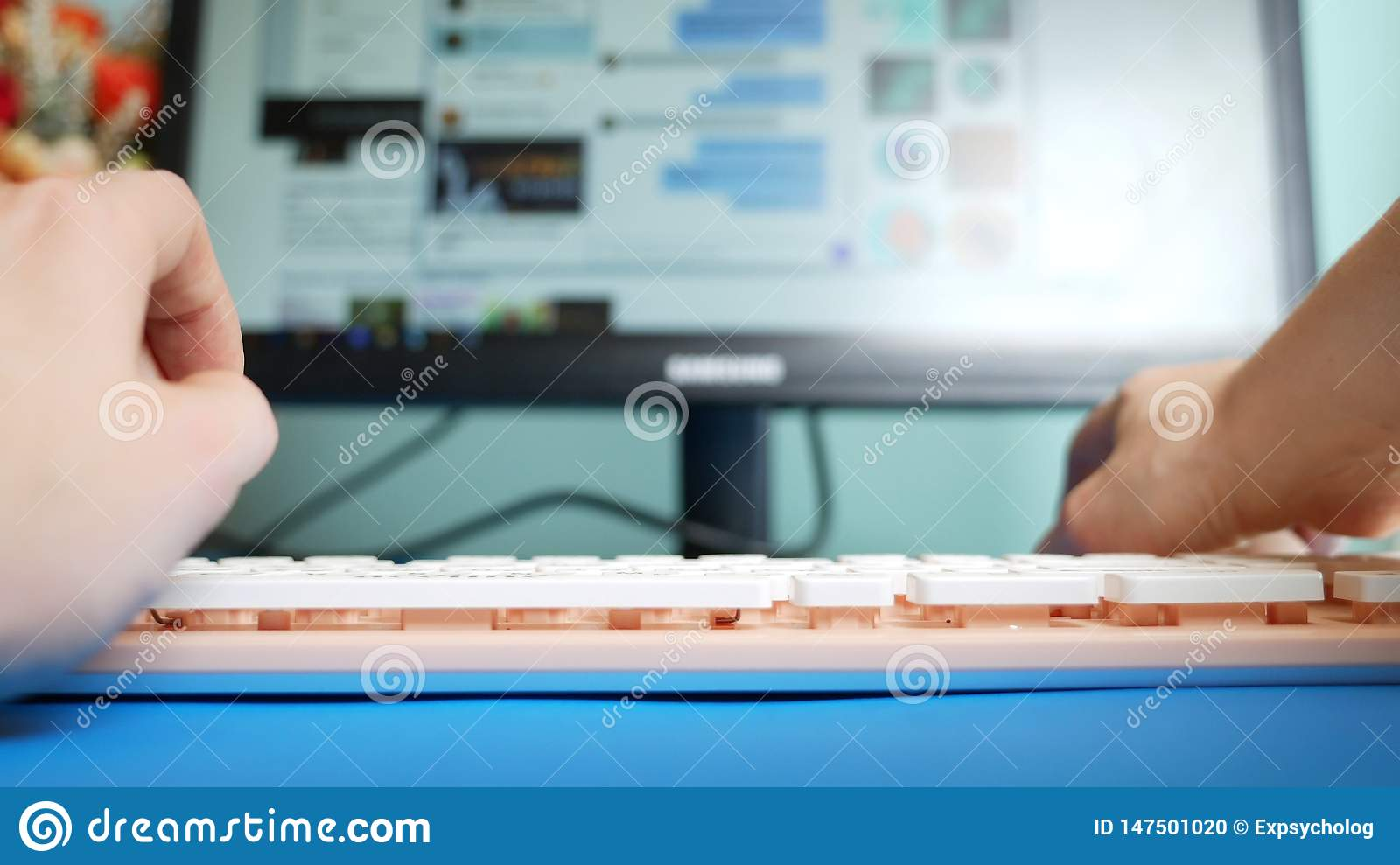 Close-up. first-person view. Female hands typing on a pink keyboard messages in social networks, against the background