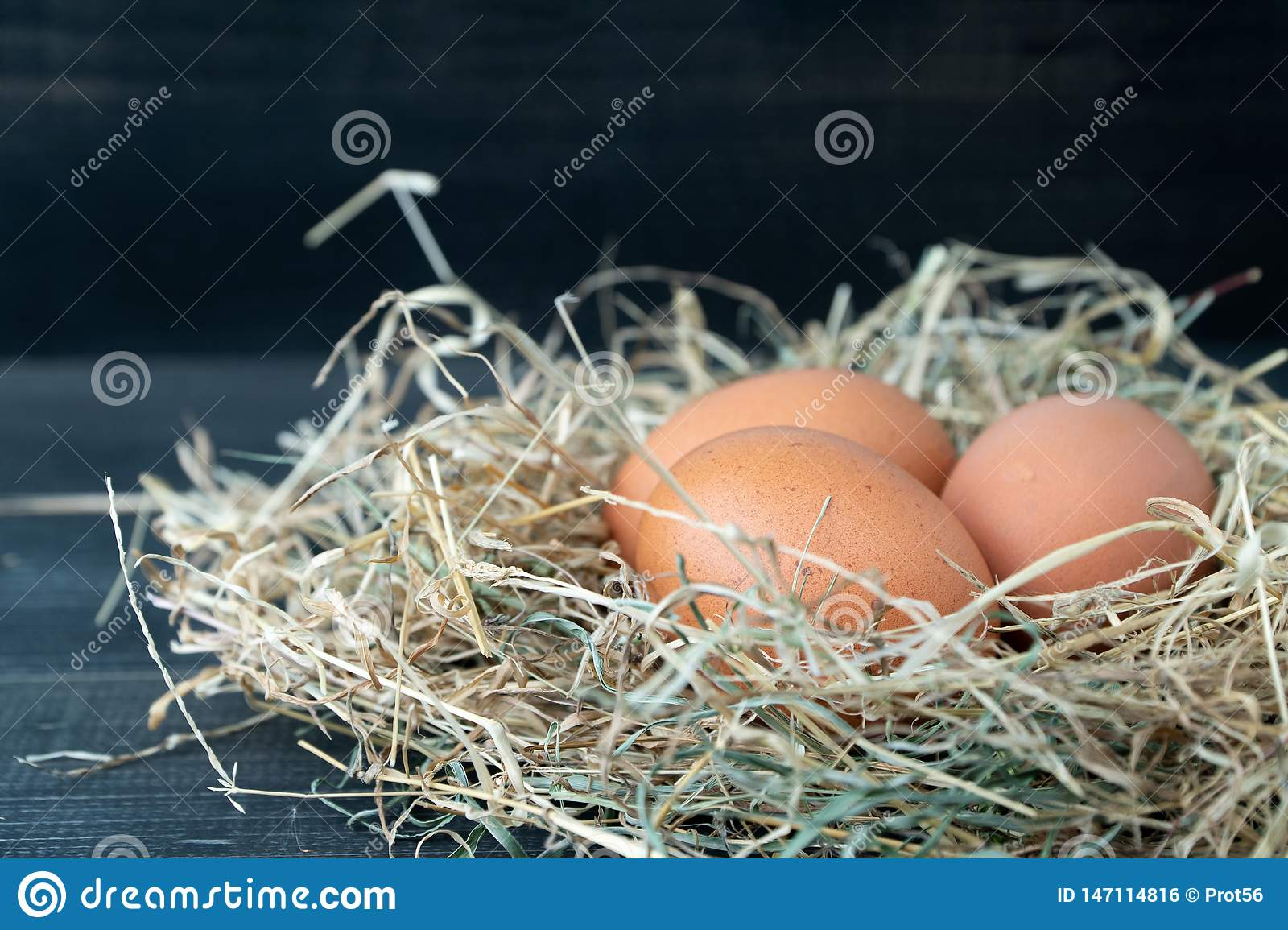 Close up of fresh brown chicken eggs in hay nest on black wooden background. Concept of organic eggs, free space for text or other