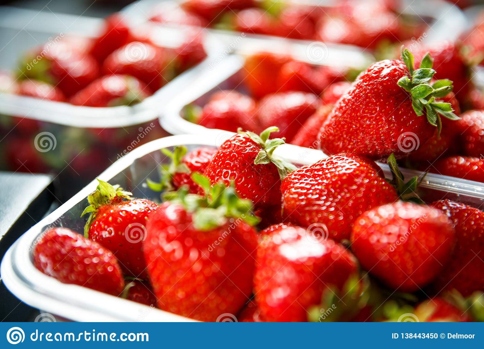 Close up of fresh red ripe strawberries in transparent plastic container boxes