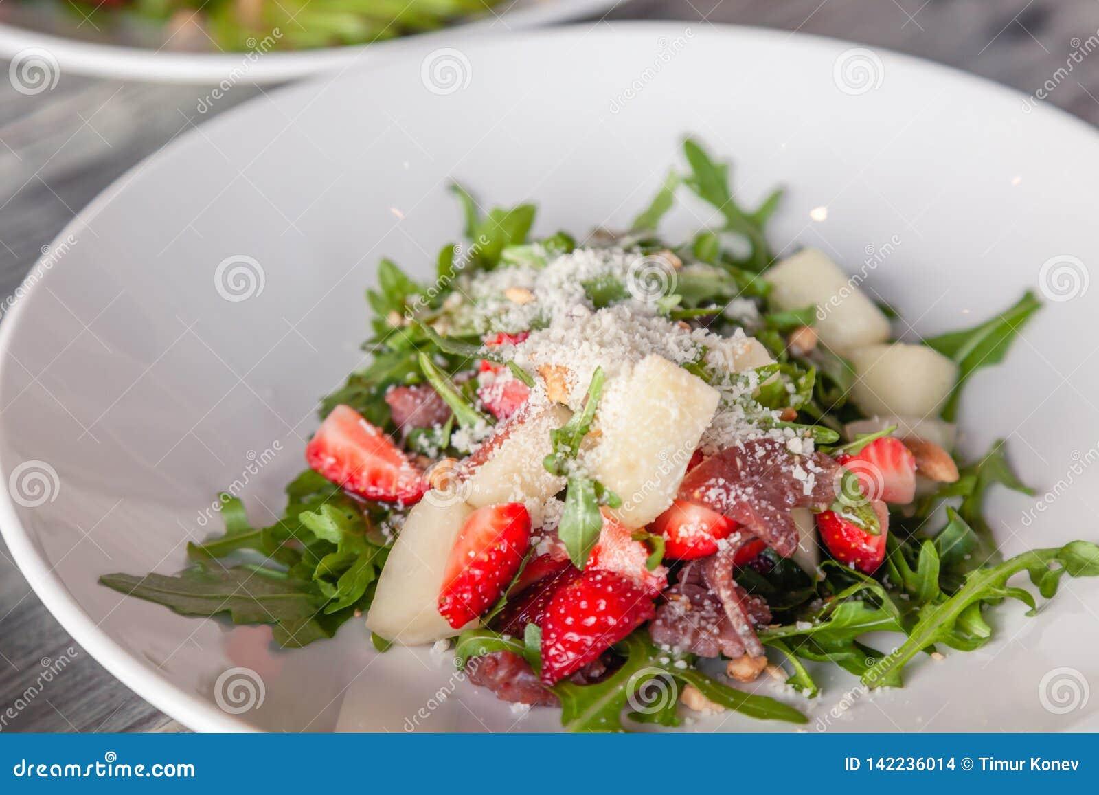 Close-up fresh summer salad with basturma jerky, greens, arugula, strawberries, melon, parmesan cheese. Concept delicacy, new menu