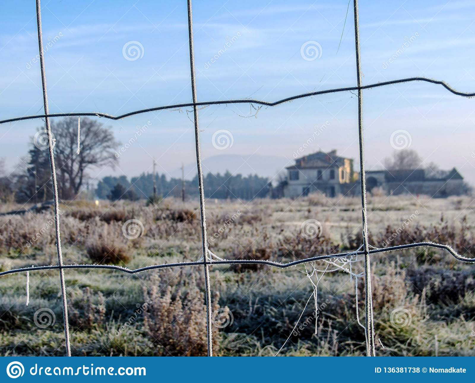 Close up of frosted metal mesh fence and typical old French house on the background