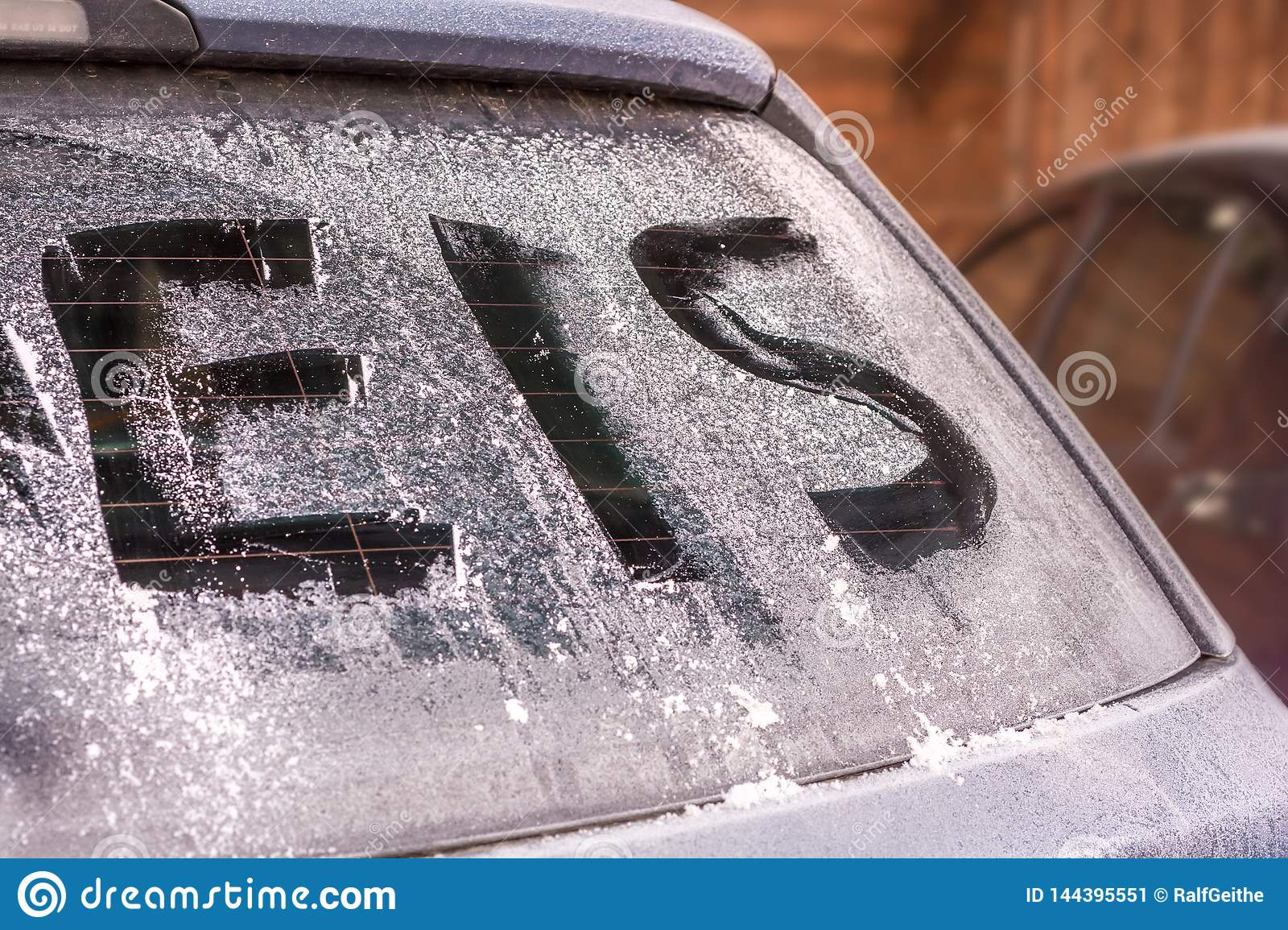 Icy rear window of a car with the german word for ice