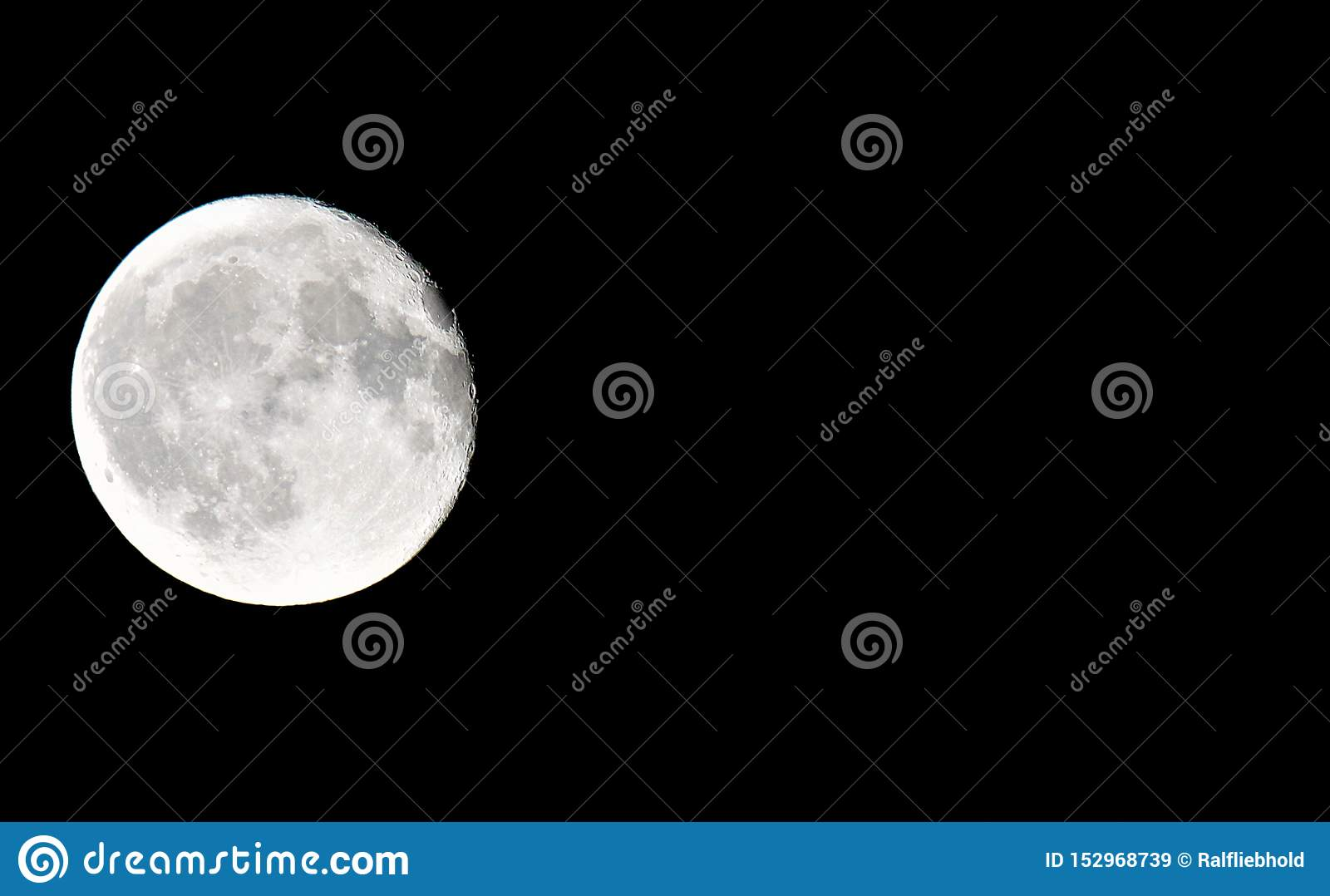 Close up of full moon with black background on left side of photo with copy space