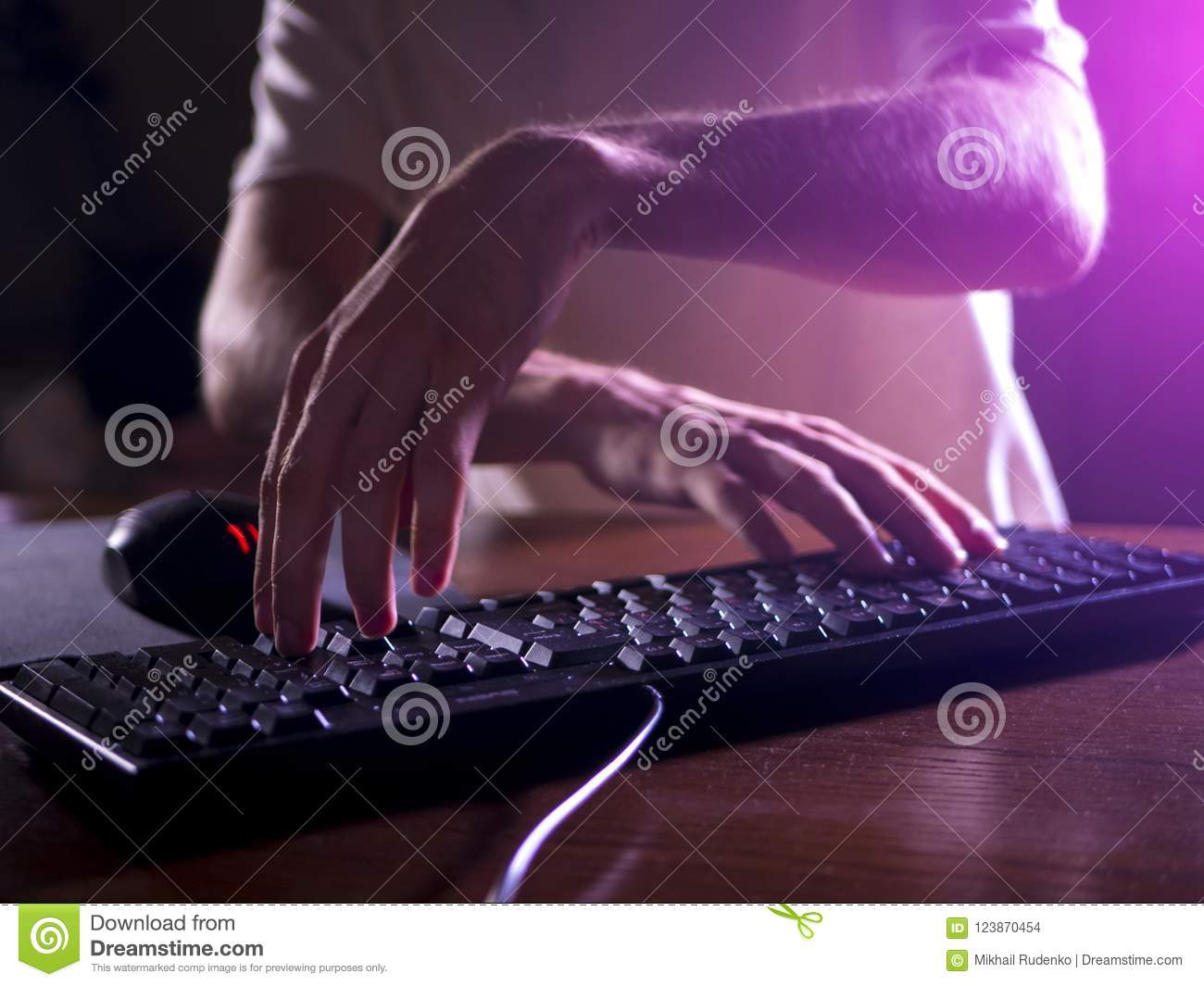Close up gamer hands on the keyboard playing video games in night
