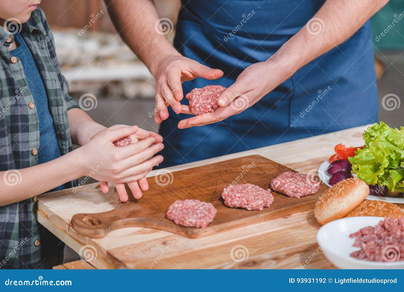 Close-up gedeeltelijke mening van vader en zoons het koken burgers op houten scherpe raad